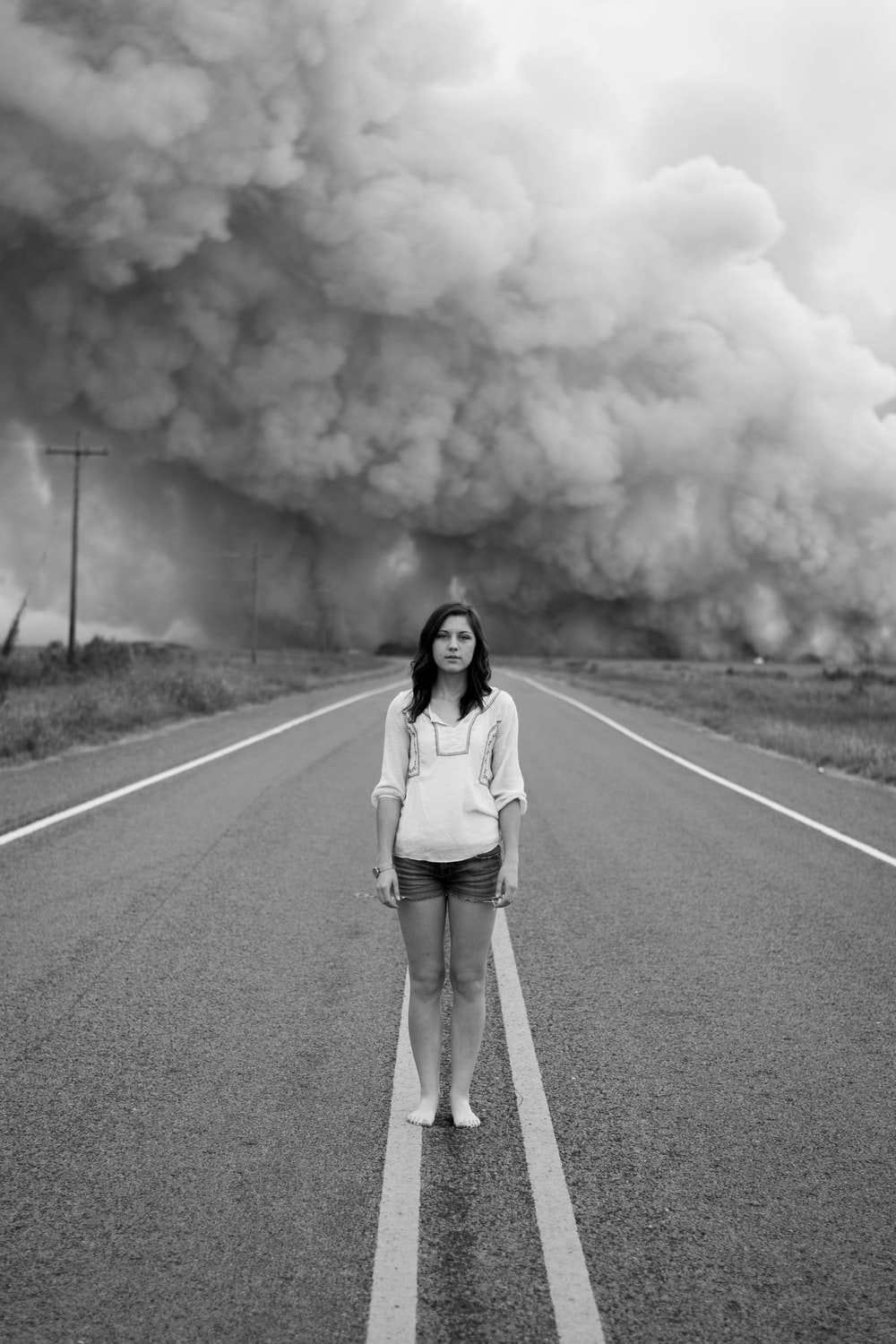 Grayscale Photo Of Woman Standing In The Middle Of The Road
