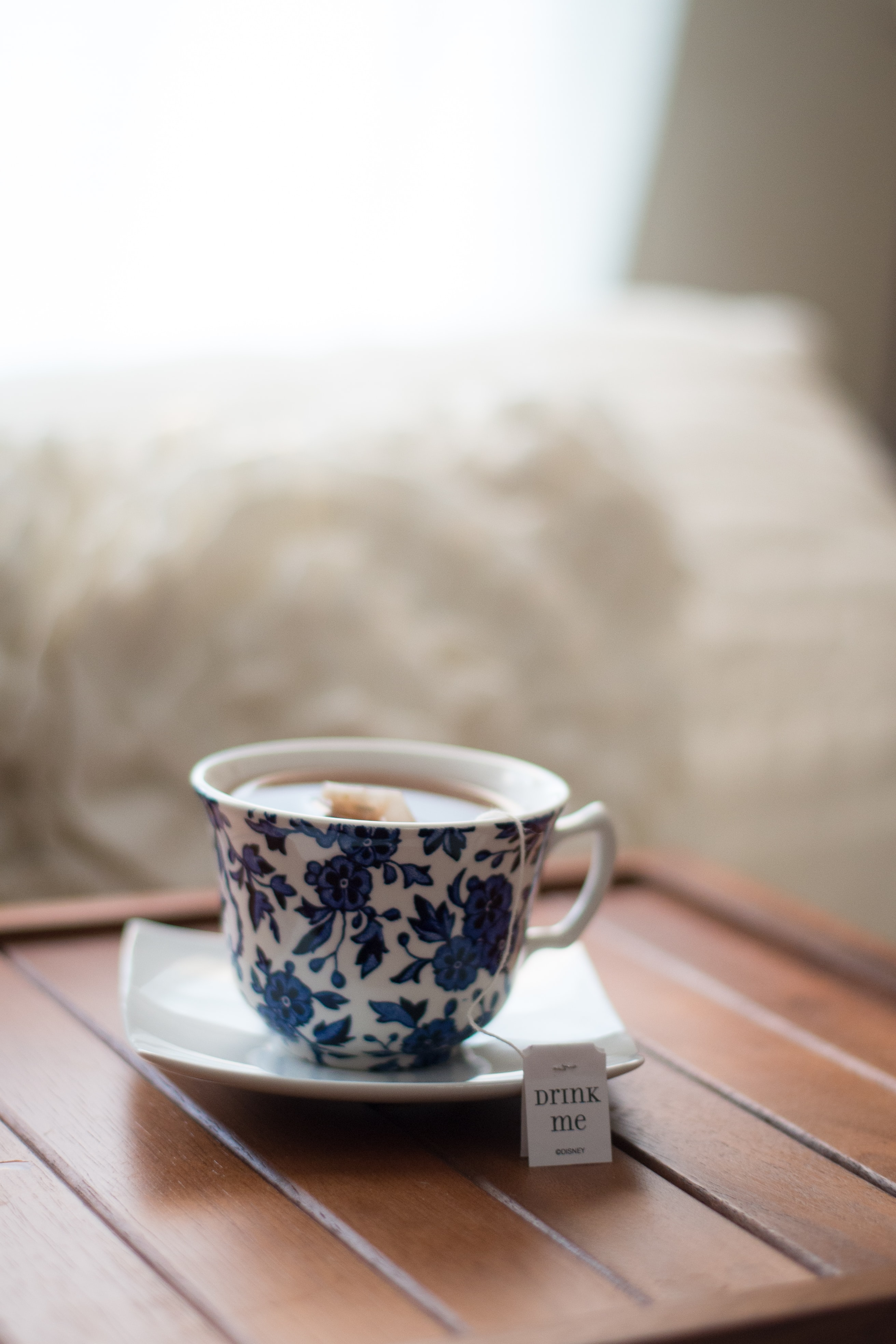 white and blue floral teacup with tea bag in saucer in tilt shift photography