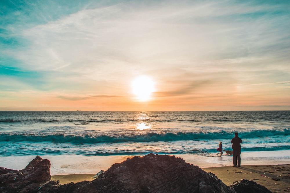 man on beach during sunset