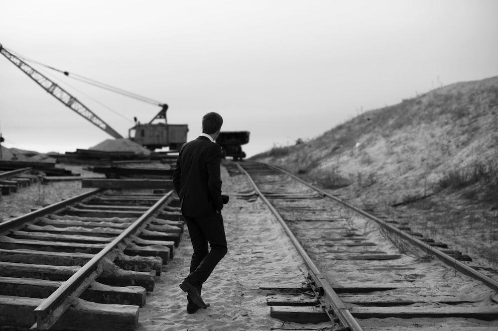 grayscale of man walking on train rail