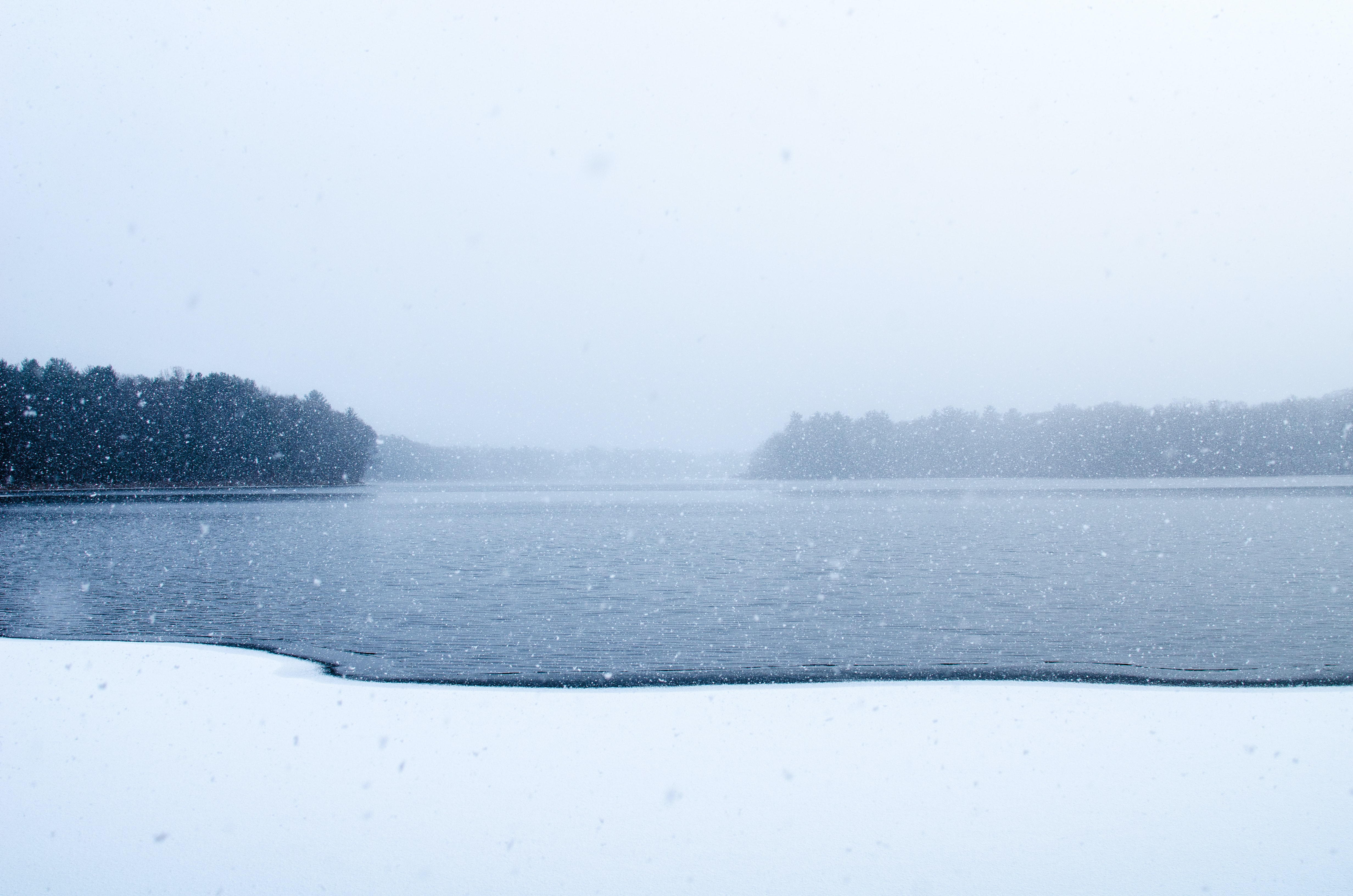 Snow falls on a dark, frozen lake surrounded by tees