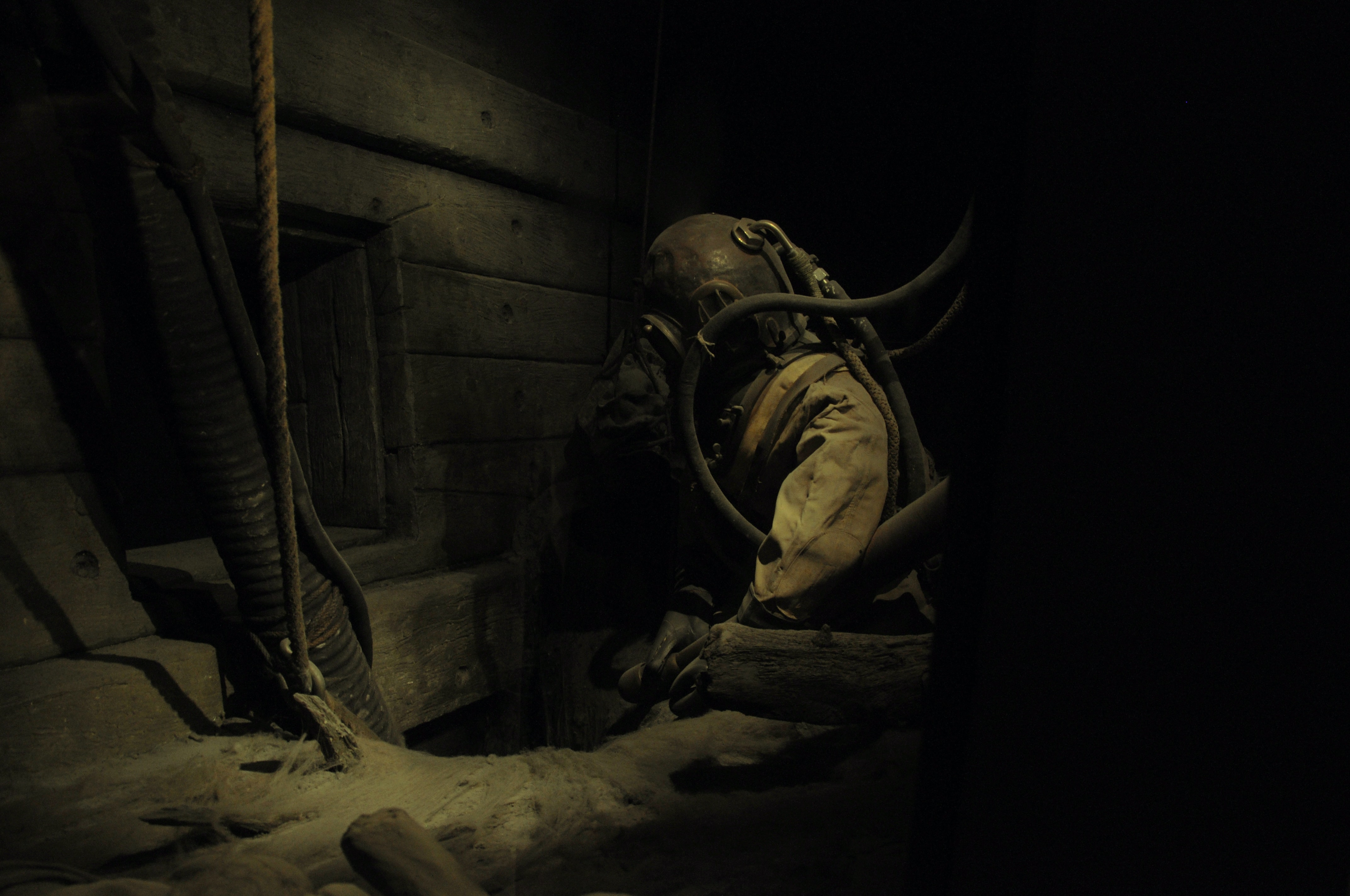 A rusty antique diver suit in a dark basement