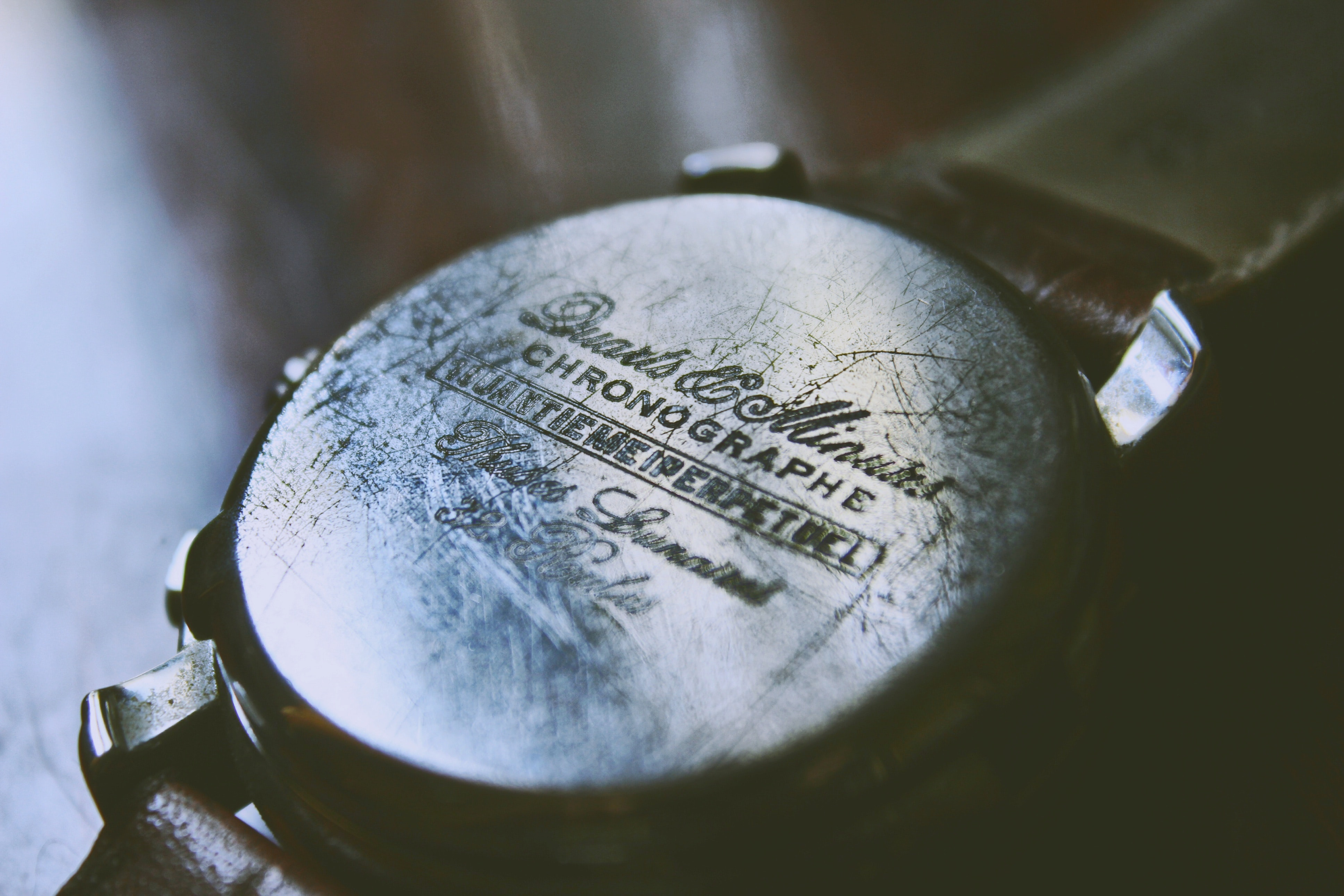 Scuffed back of a vintage wristwatch on a wooden table