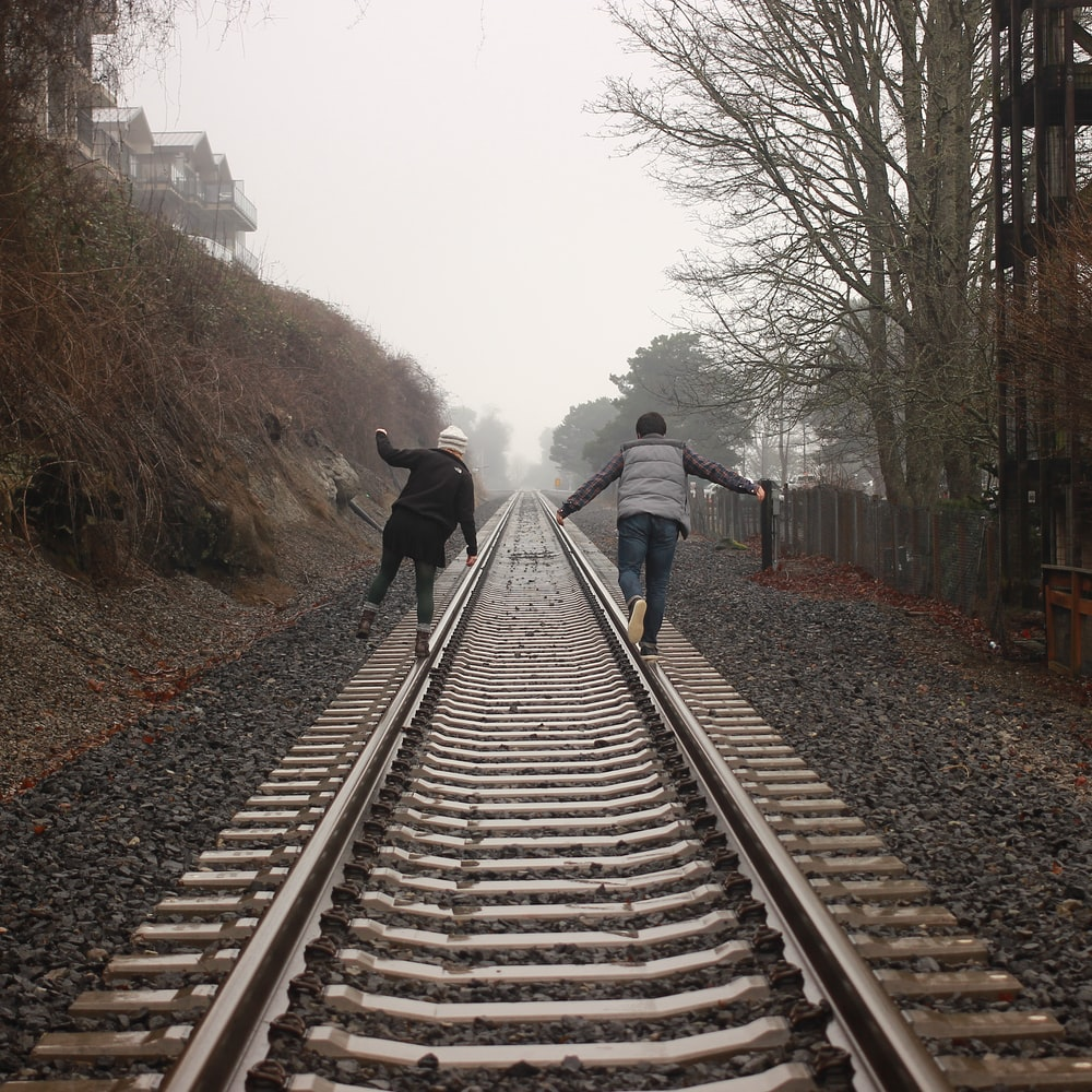 two person walking on the train rail