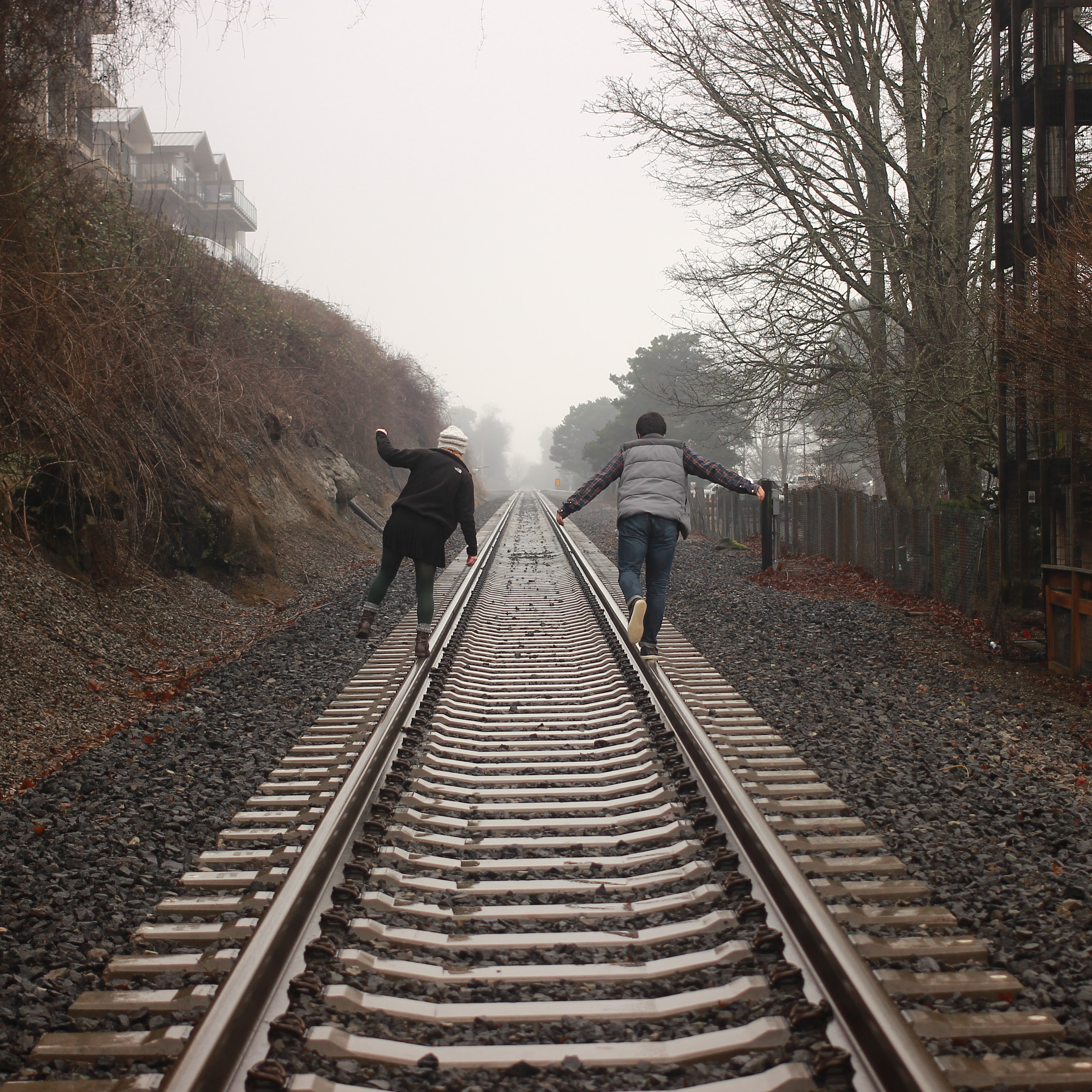 Two people balancing on the rails of a train track during a foggy day