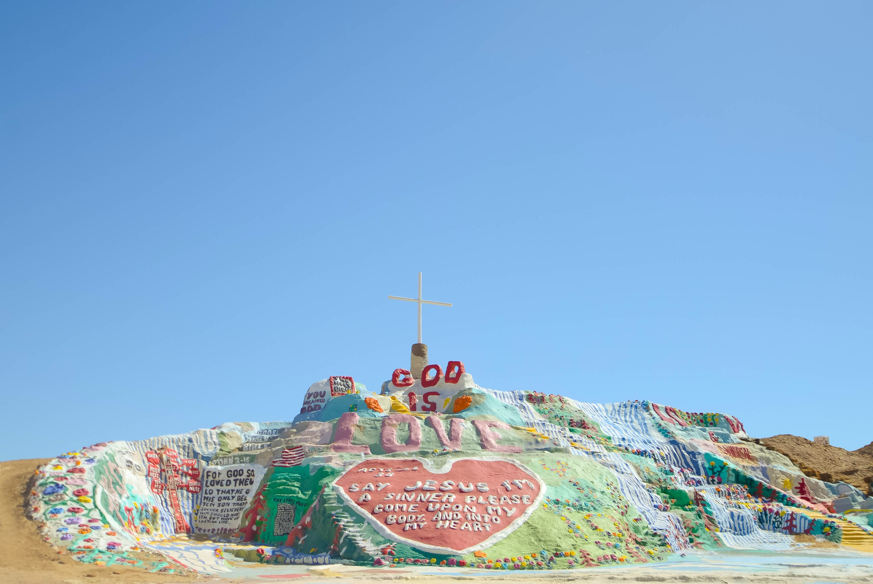 """Salvation Mountain, a colorful display topped by a cross, reads """"God is Love"""" against blue sky"""