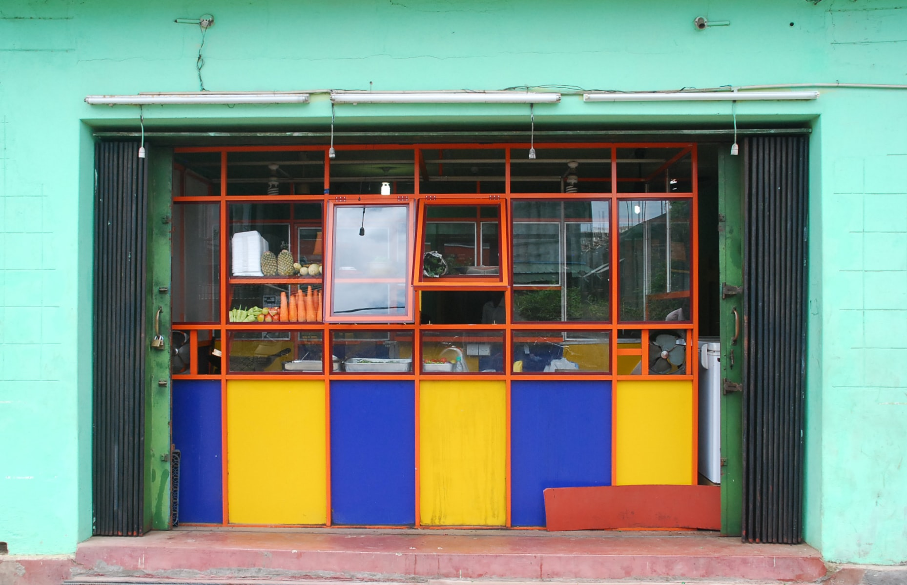 A store window with yellow and blue tiles below