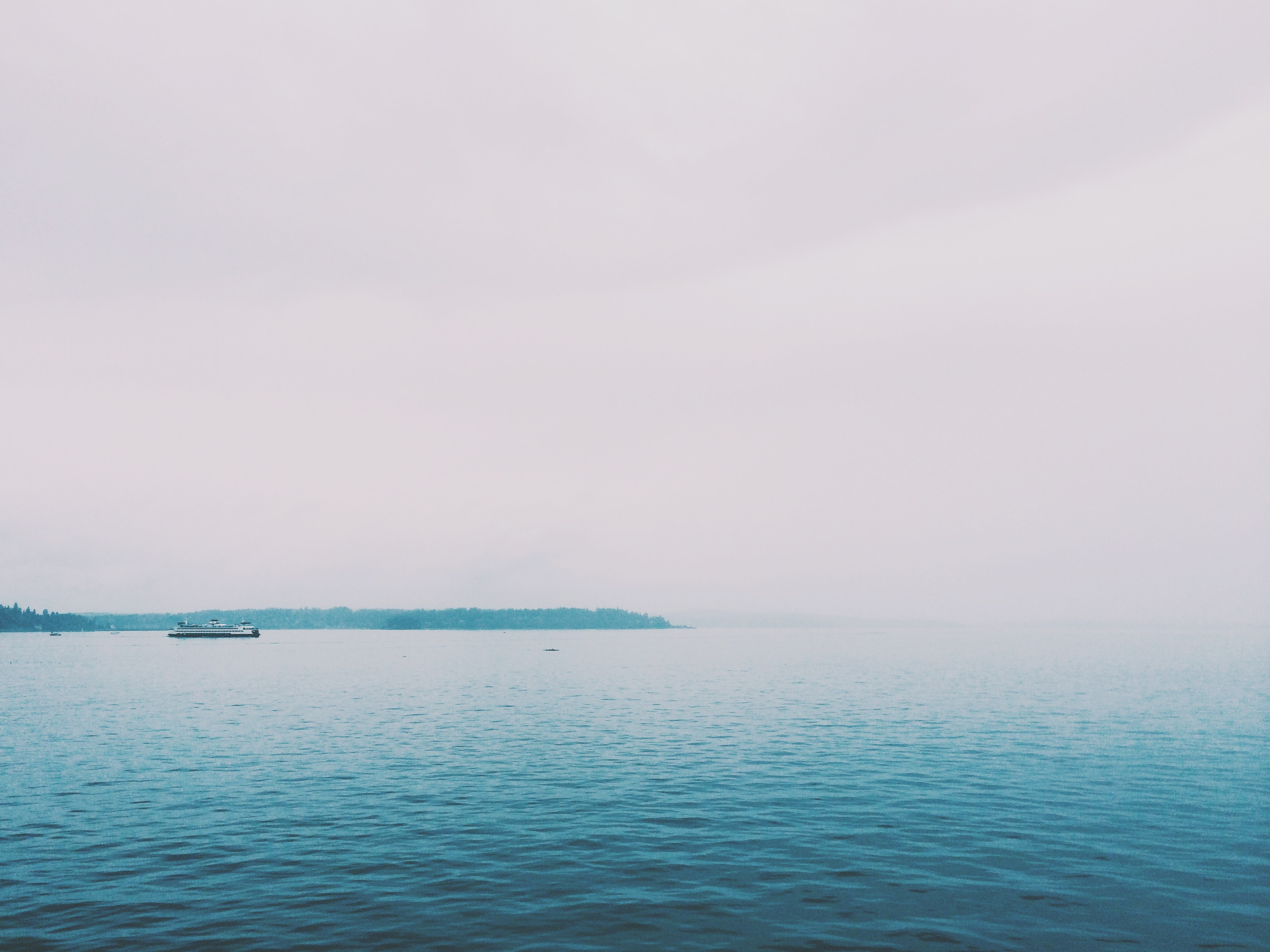 Boat passes through calm ripples on a foggy day on the water
