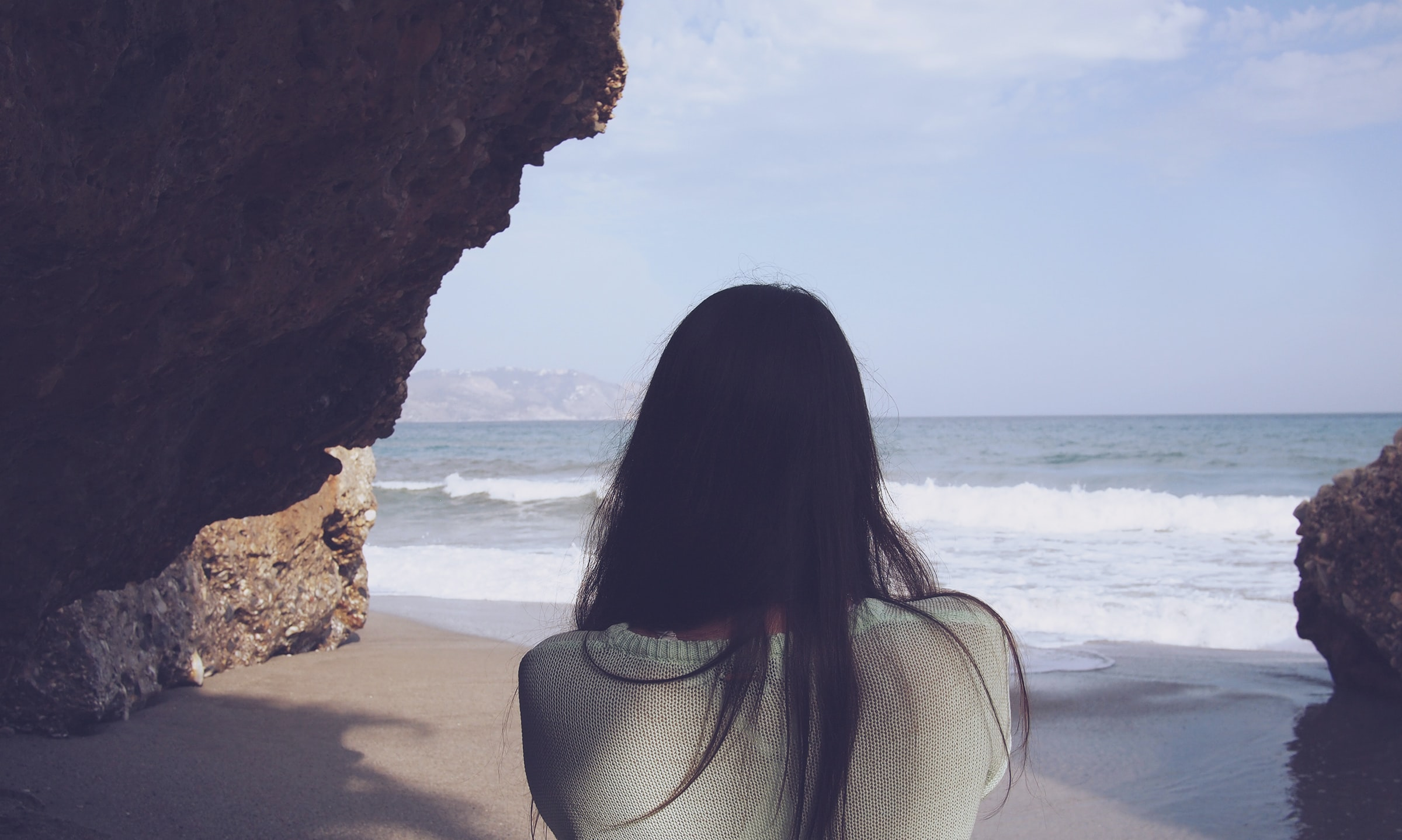 A dark-haired woman looking at the crashing sea waves under a cliff