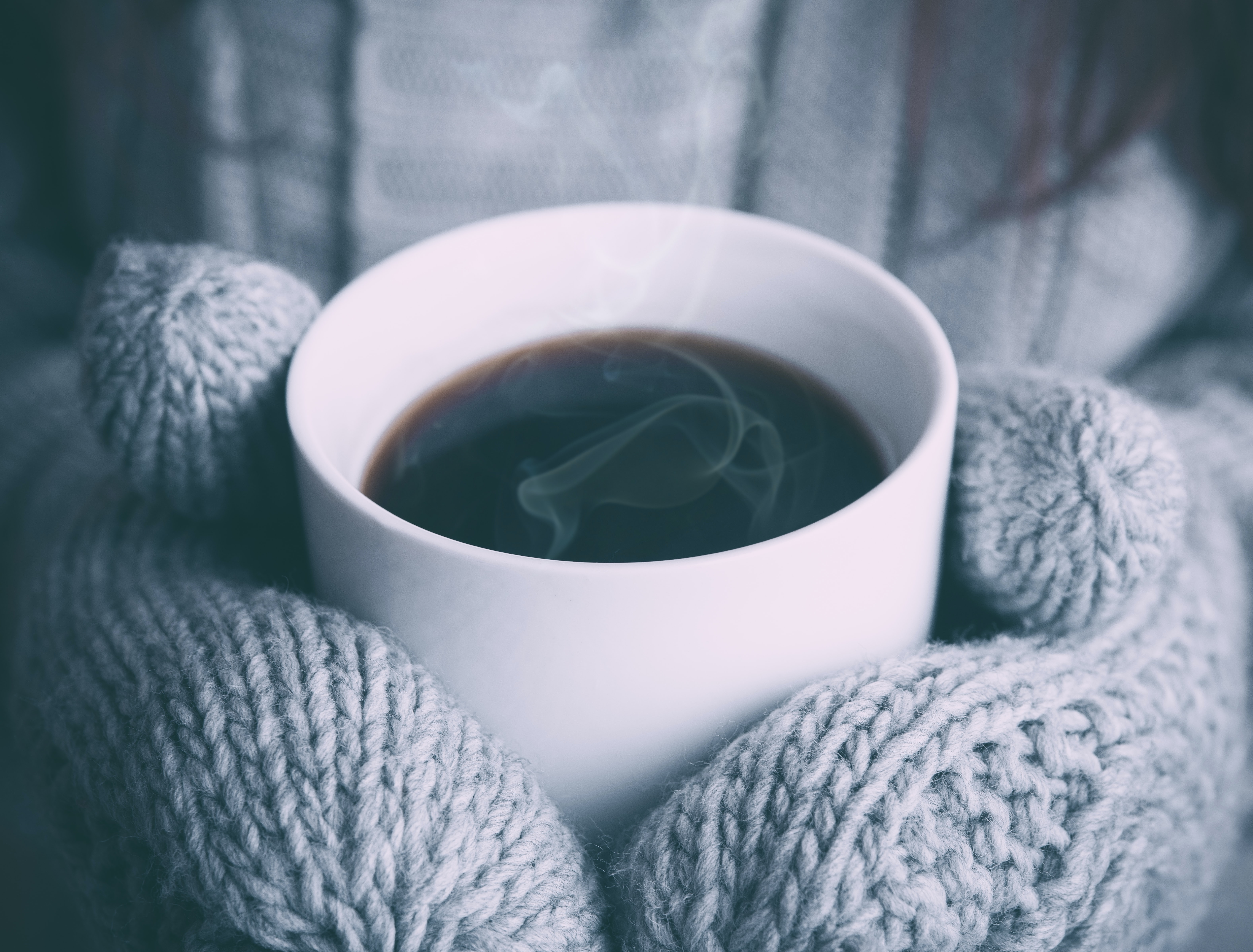A person in mittens holding a cup of hot coffee