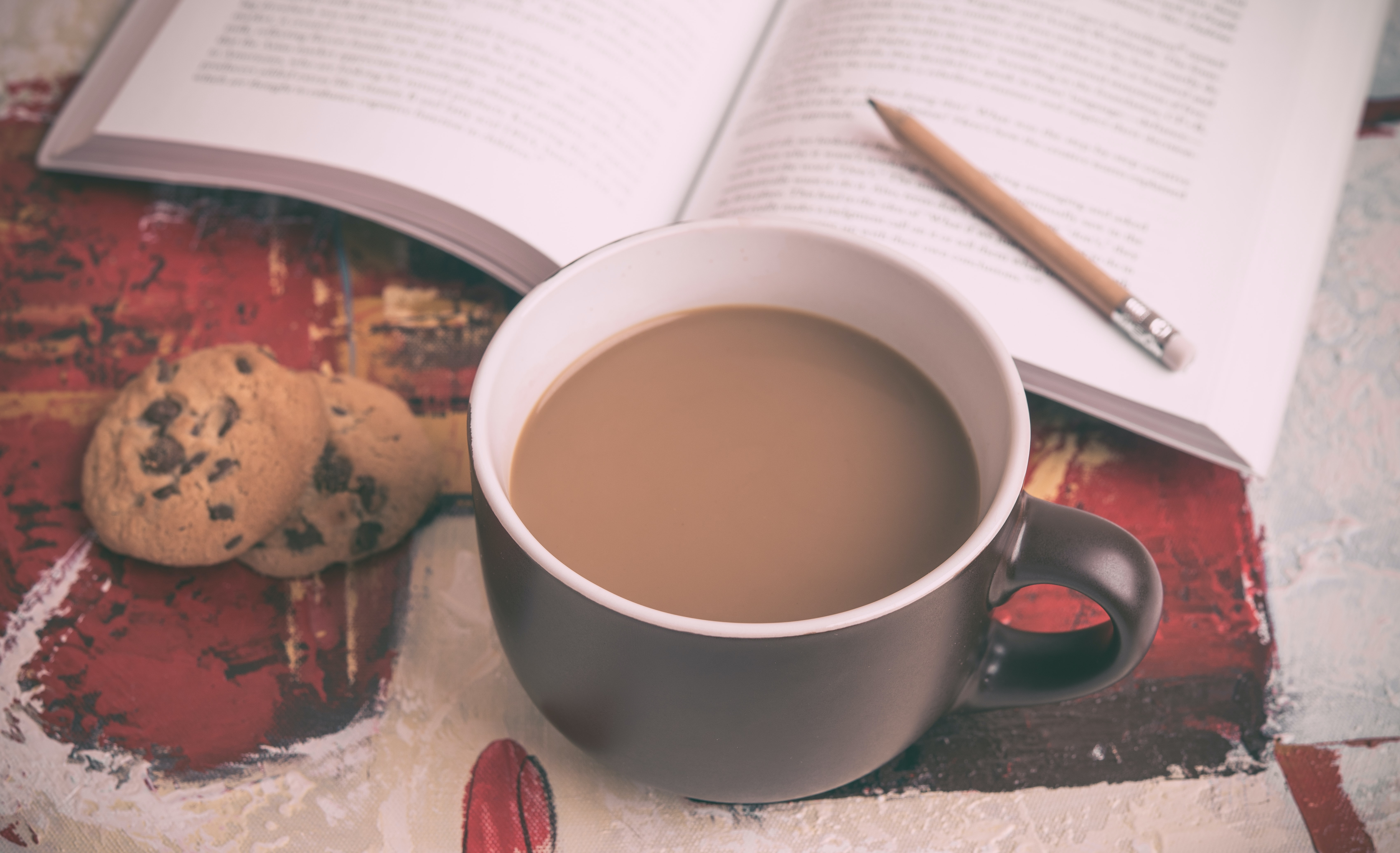 A cup of coffee in a brown mug next to some chocolate chip cookies and a book on a table