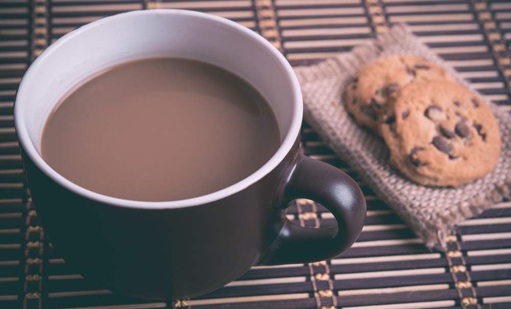 white and brown ceramic cup with coffee near cookies