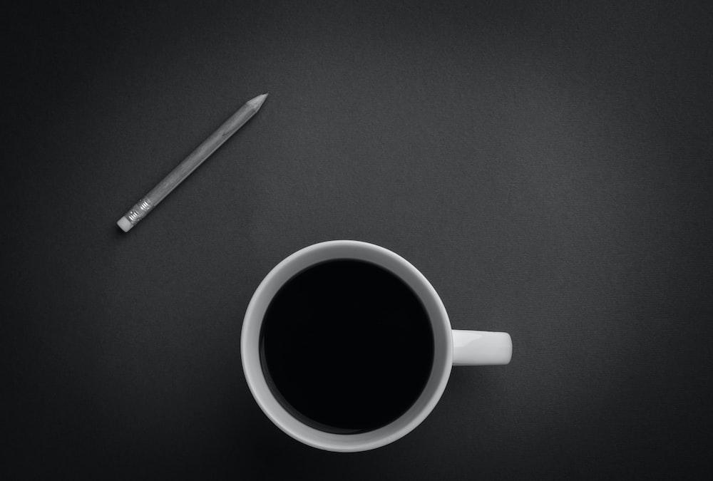 white ceramic teacup near gray pencil on black surface