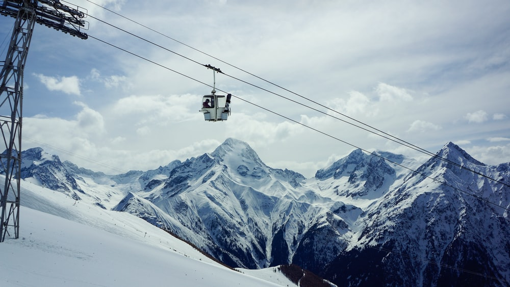 white cable car passing under snowfield during daytime