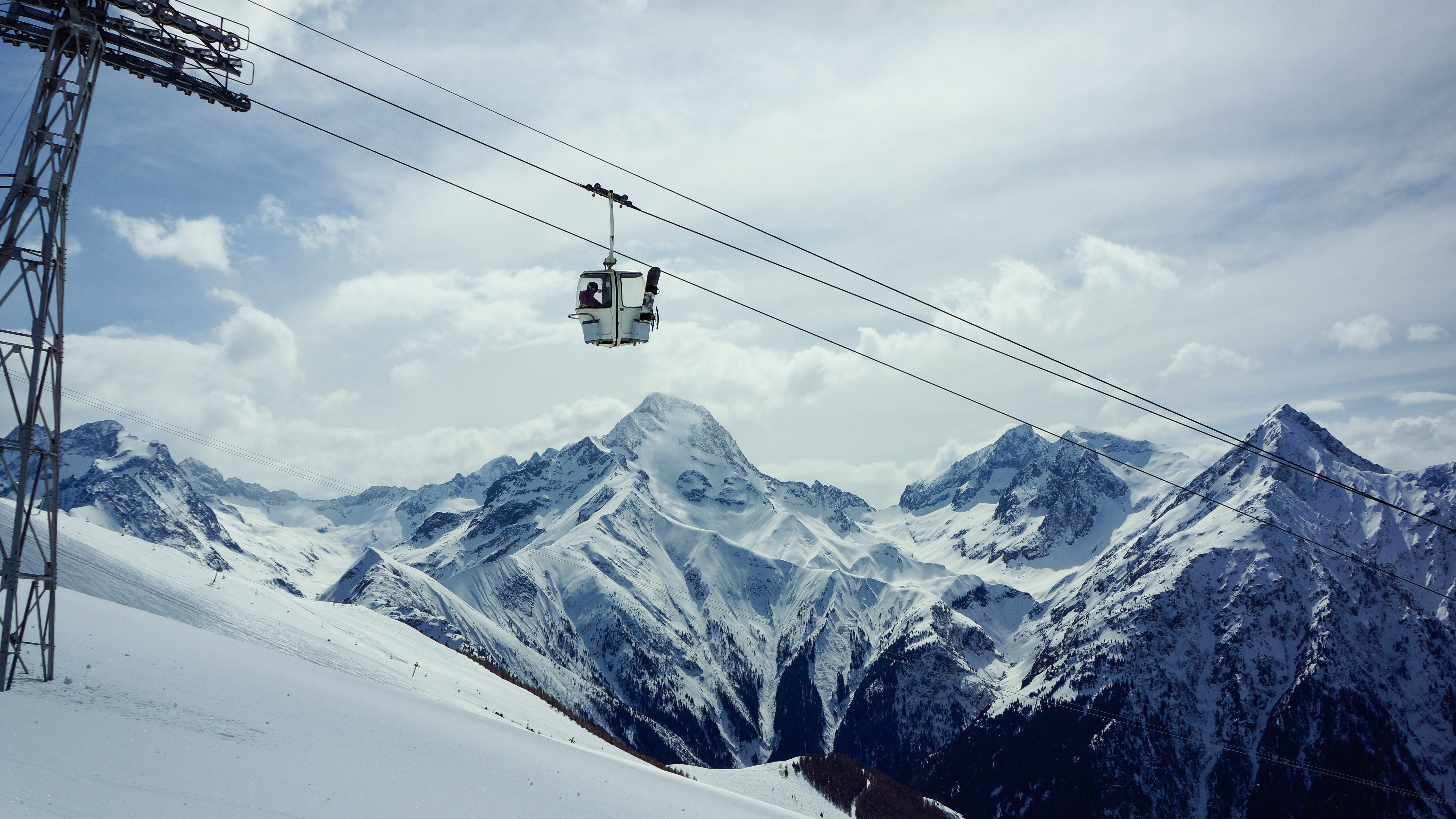 A white chairlift going up with big mountain peaks in foreground