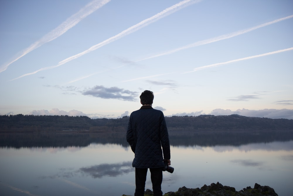 man in black top under cloudy sky