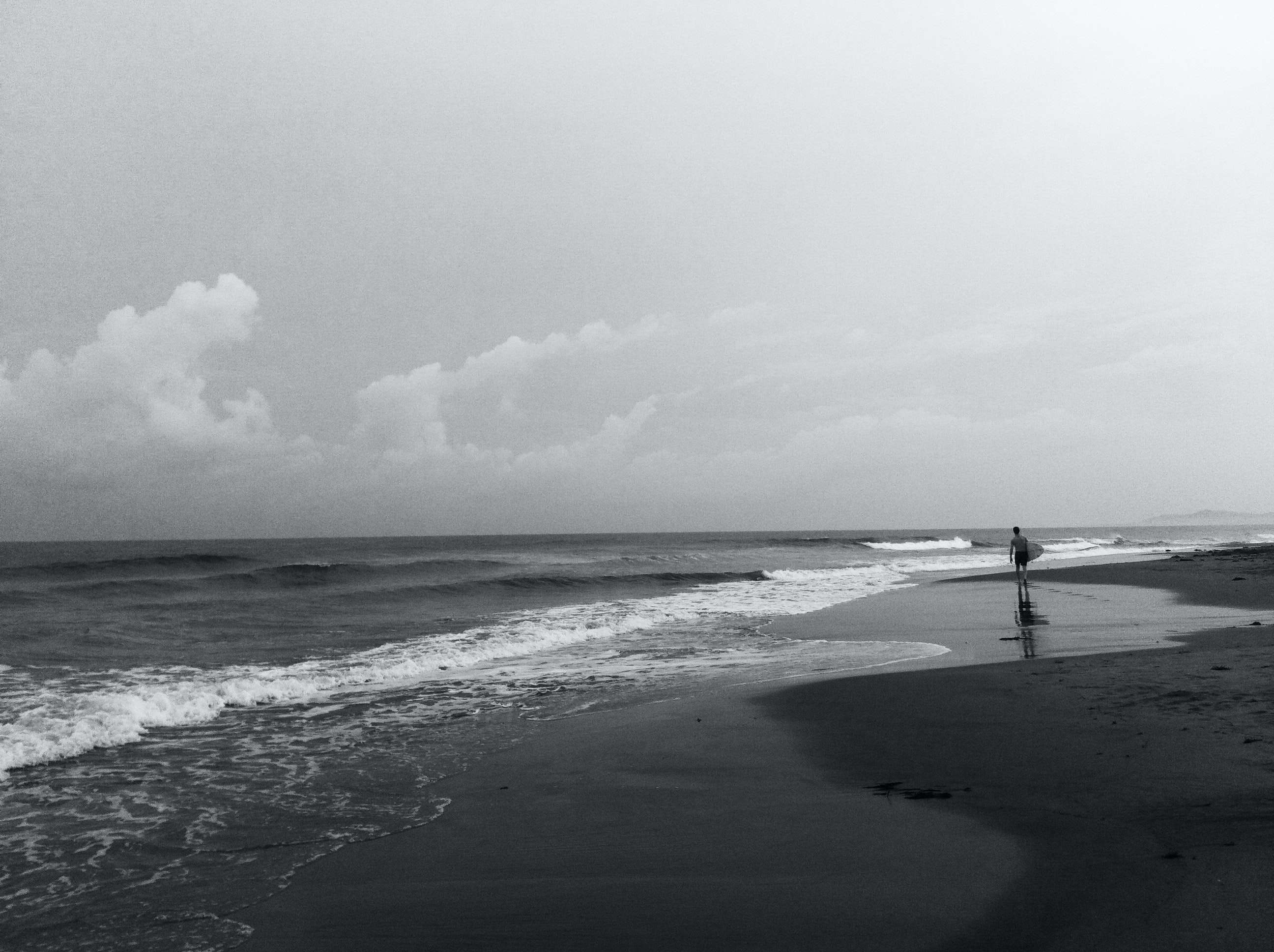 A black and white shot of a person walking a deserted beach beneath a cloudy sky