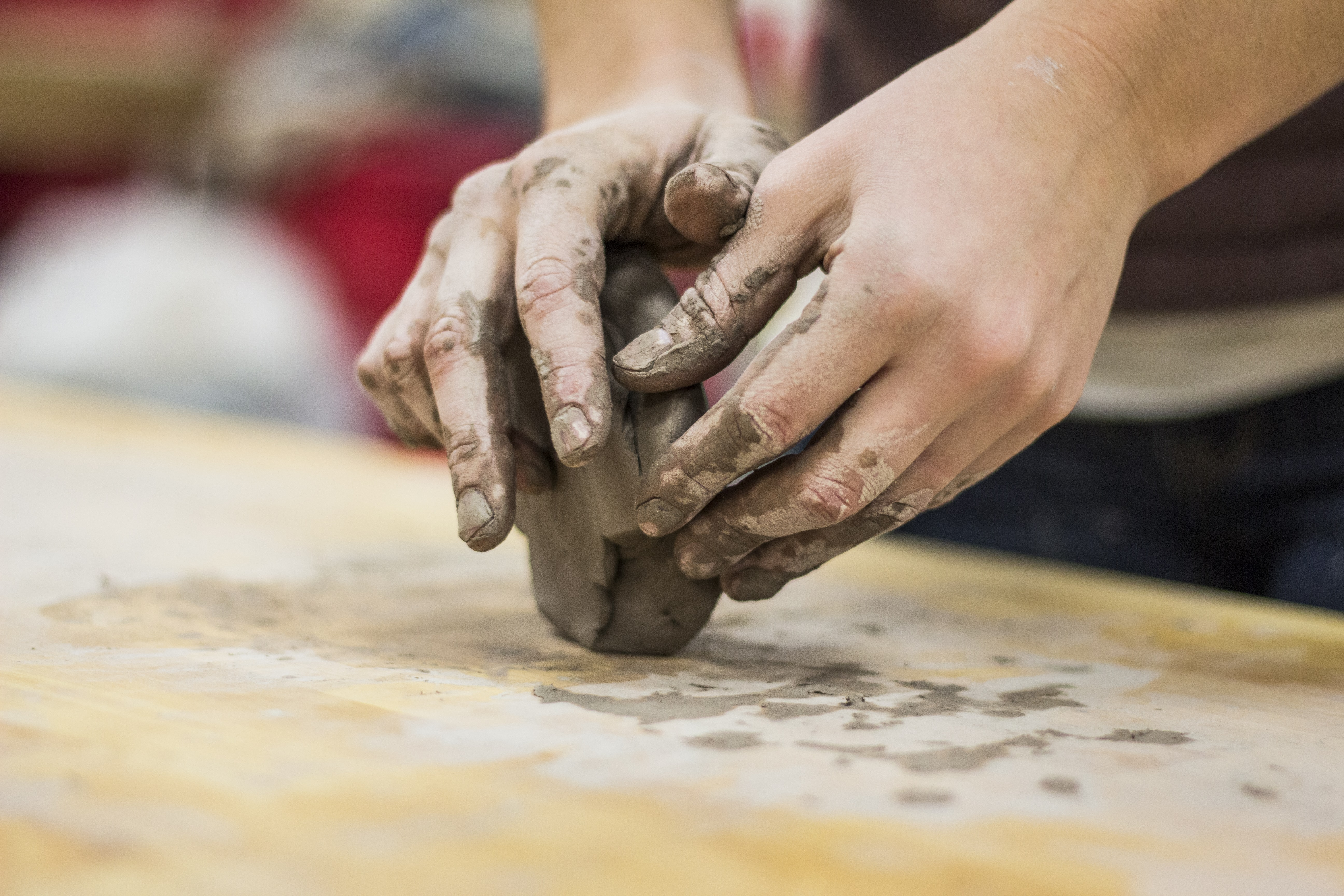 A clay stained hand of a potter engaging in a craft work of pottery or molding