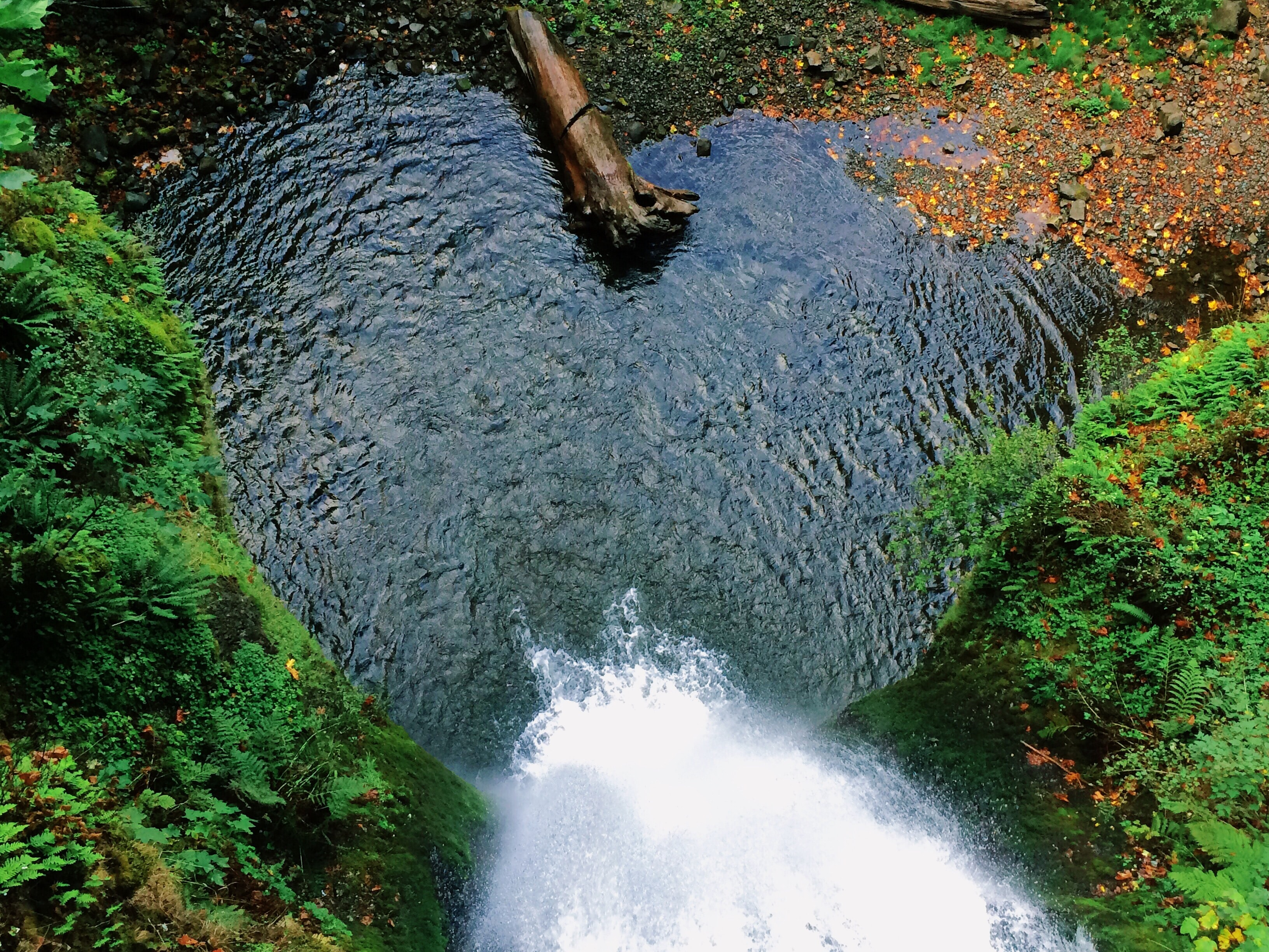 A top view of a waterfall tumbling down into a heart-shaped pond