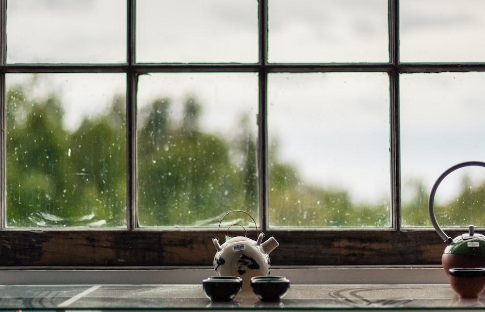 white and black cow figurine on window