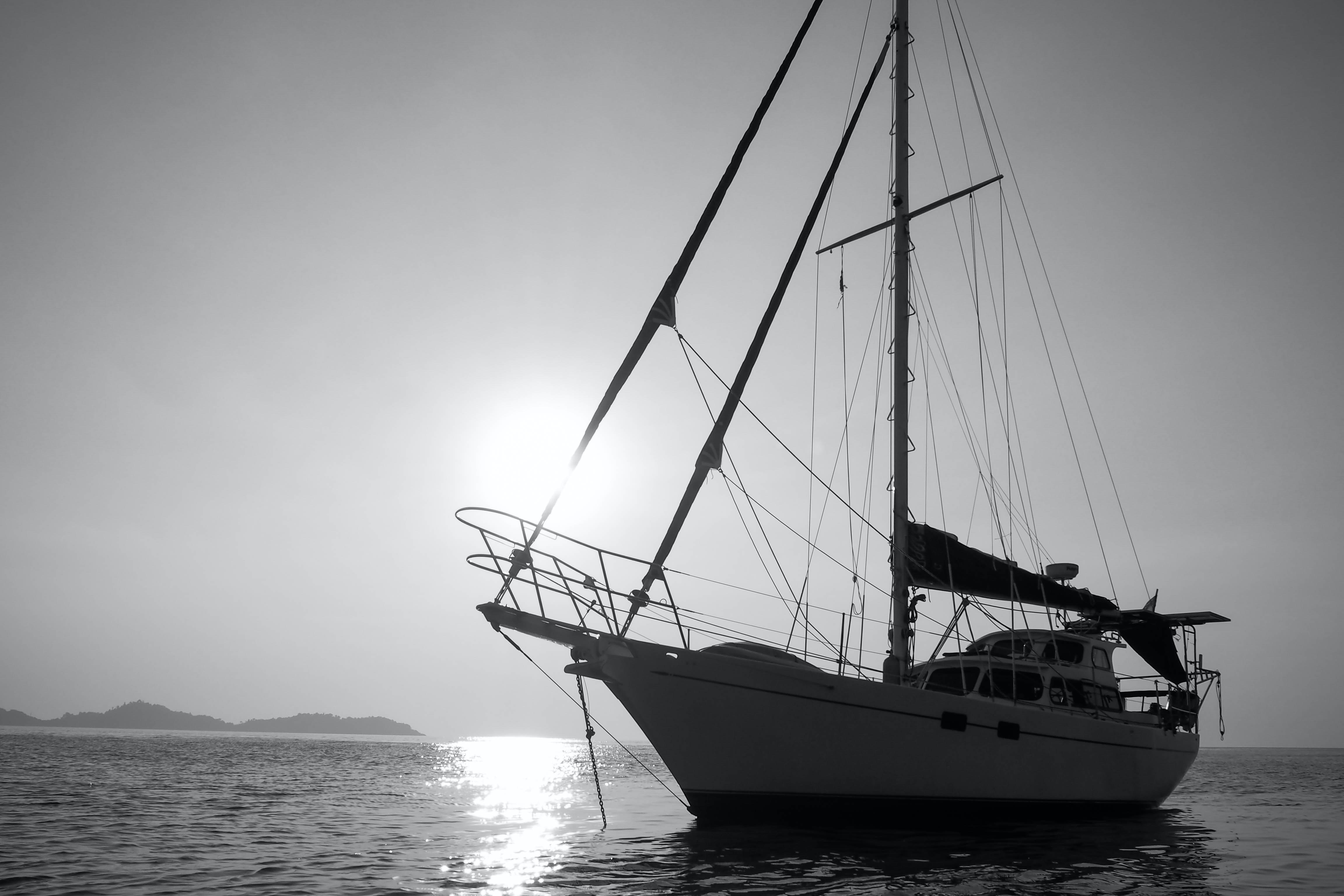 Black and white shot of yacht on sea with clear sky and sun in background