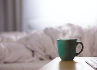 green ceramic mug on wooden desk