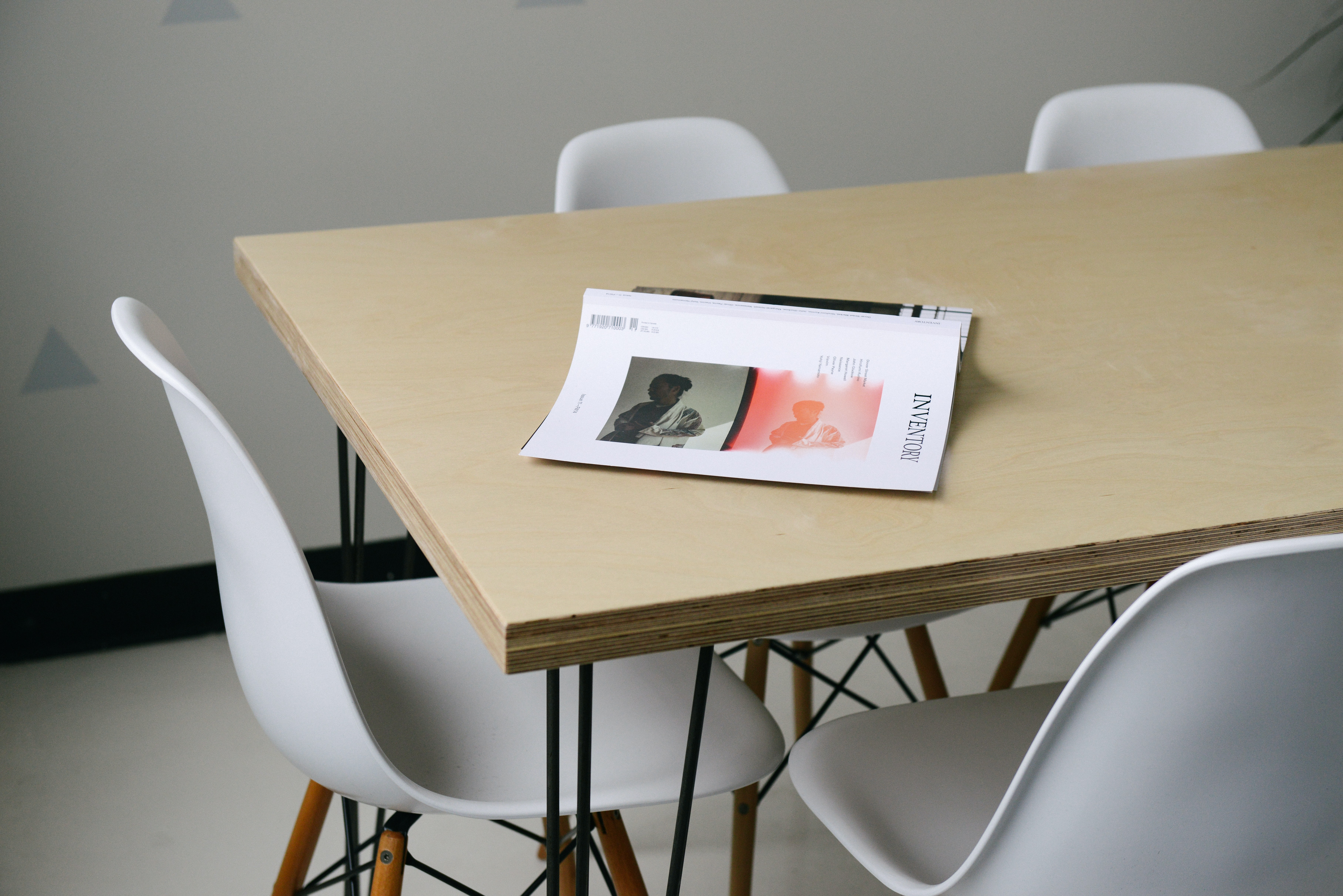 A business book turned over on a wooden table surrounded by chairs in a simple office setting