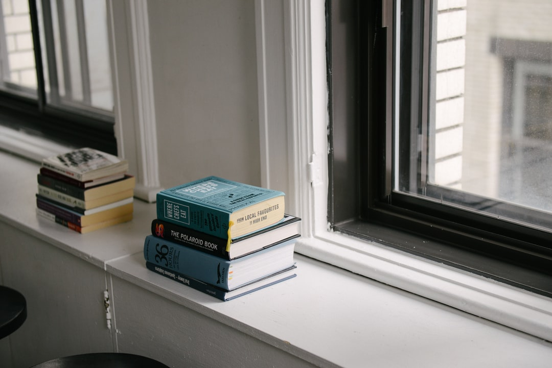 Two stacks of books on a window ledge