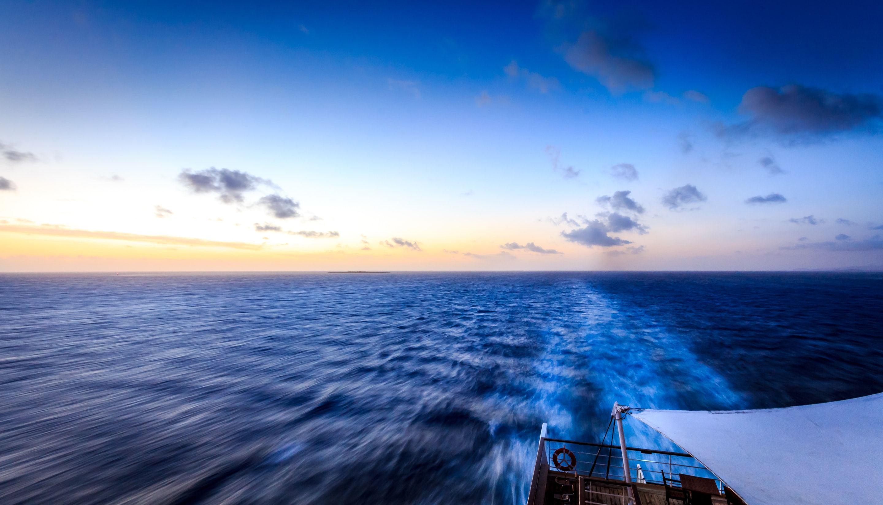 A view from the stern of a boat on its wake in deep blue ocean