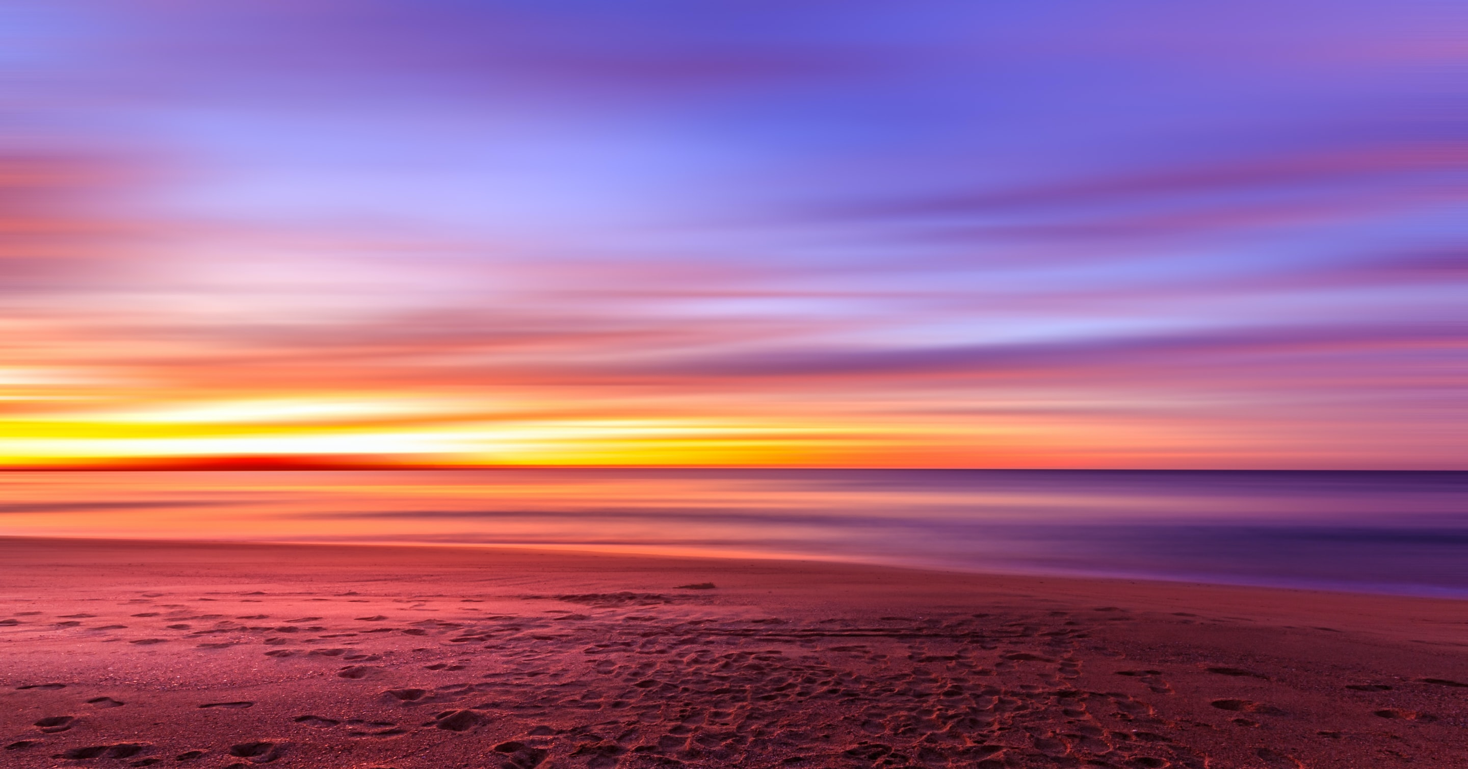 A beach with a scenic purple and orange sunset in New South Wales