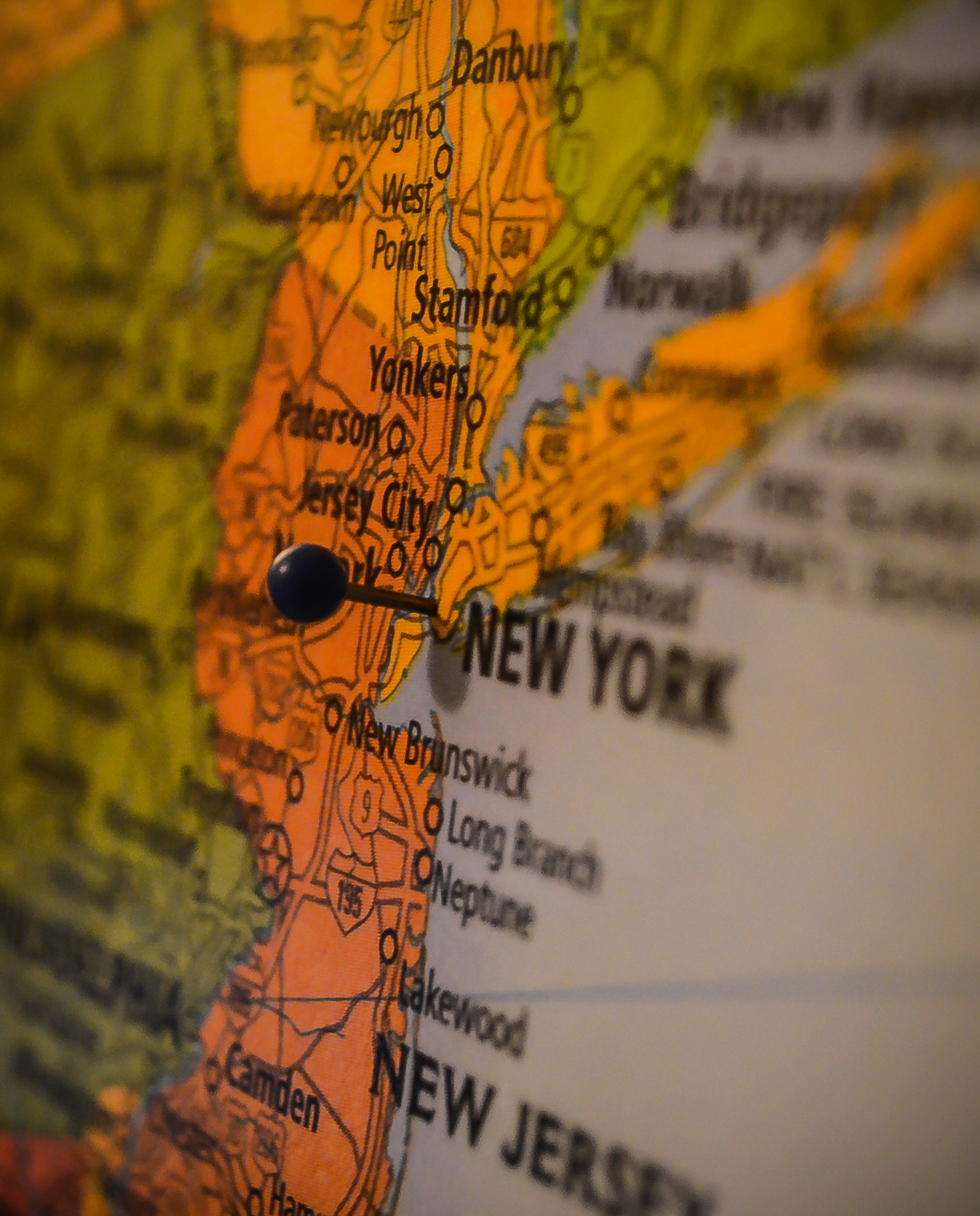 A close-up of a map with a pin stuck into it at the area of New York