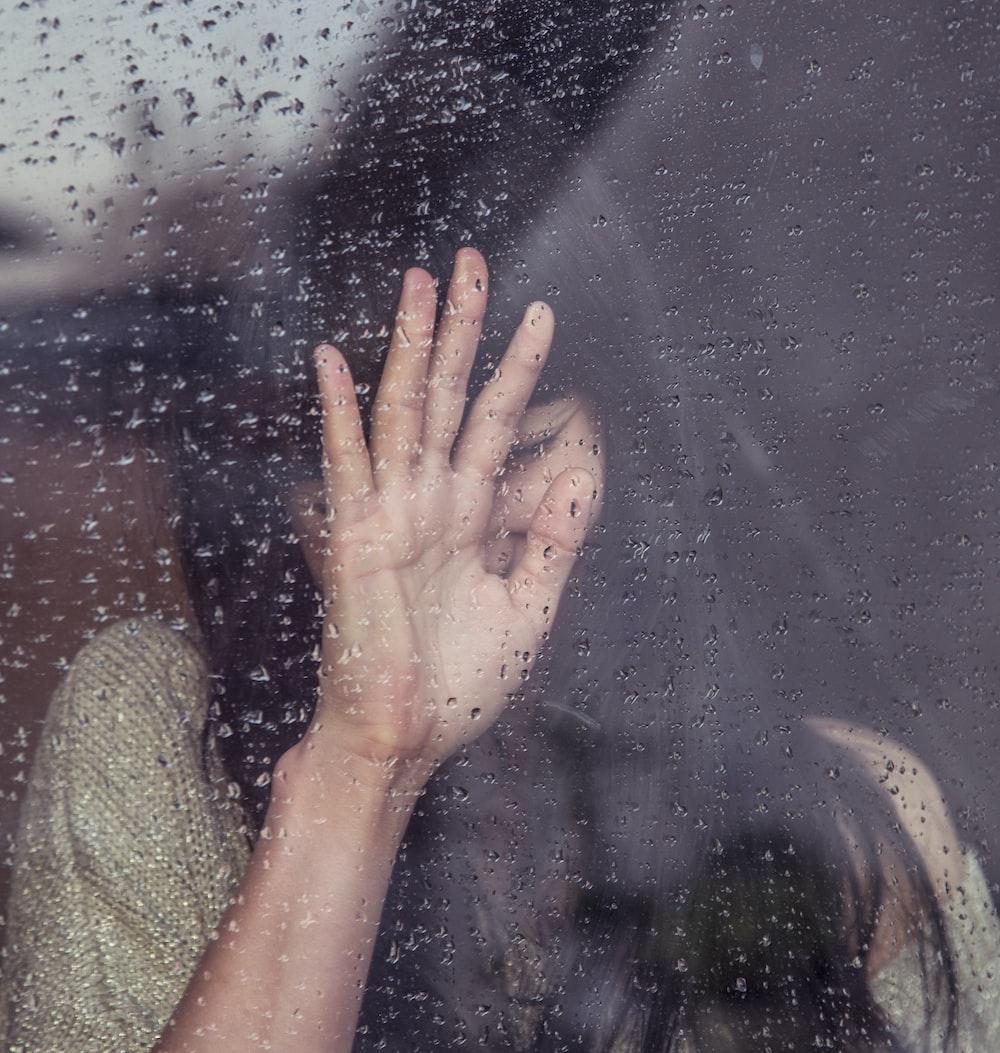 woman touch rainy glass