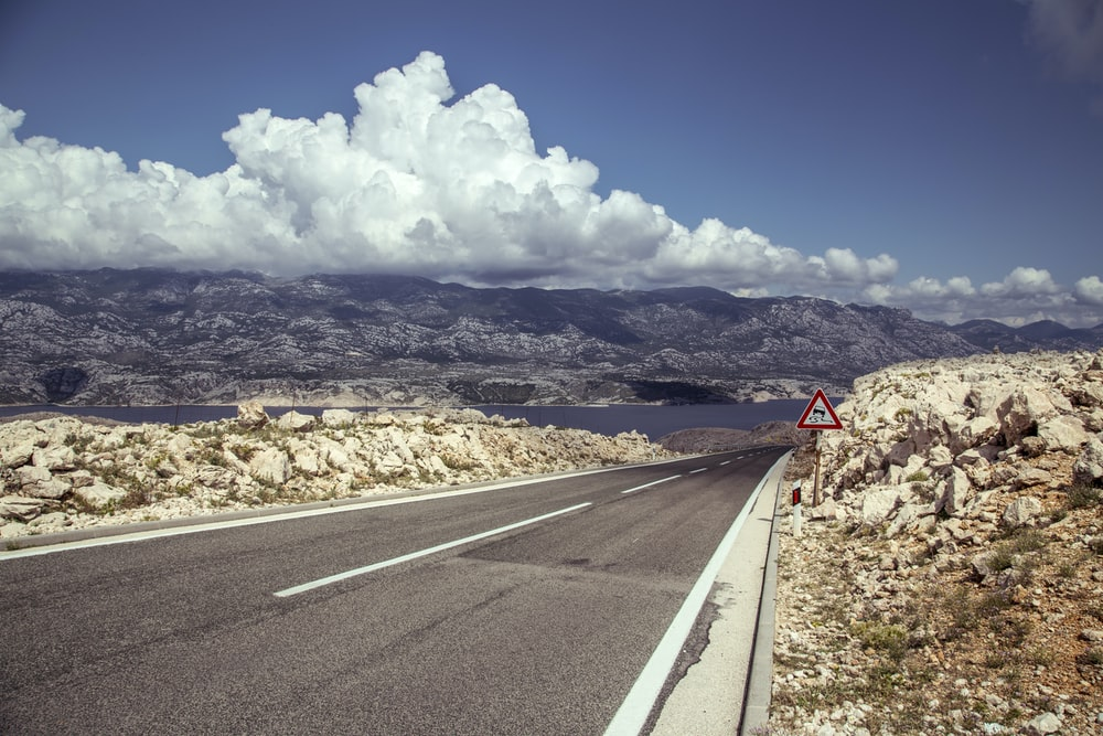 gray asphalt road under white clouds and blue sky during daytime