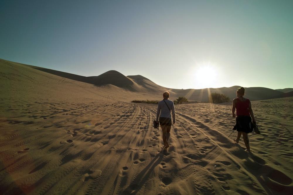 two women walking on sand during daytime