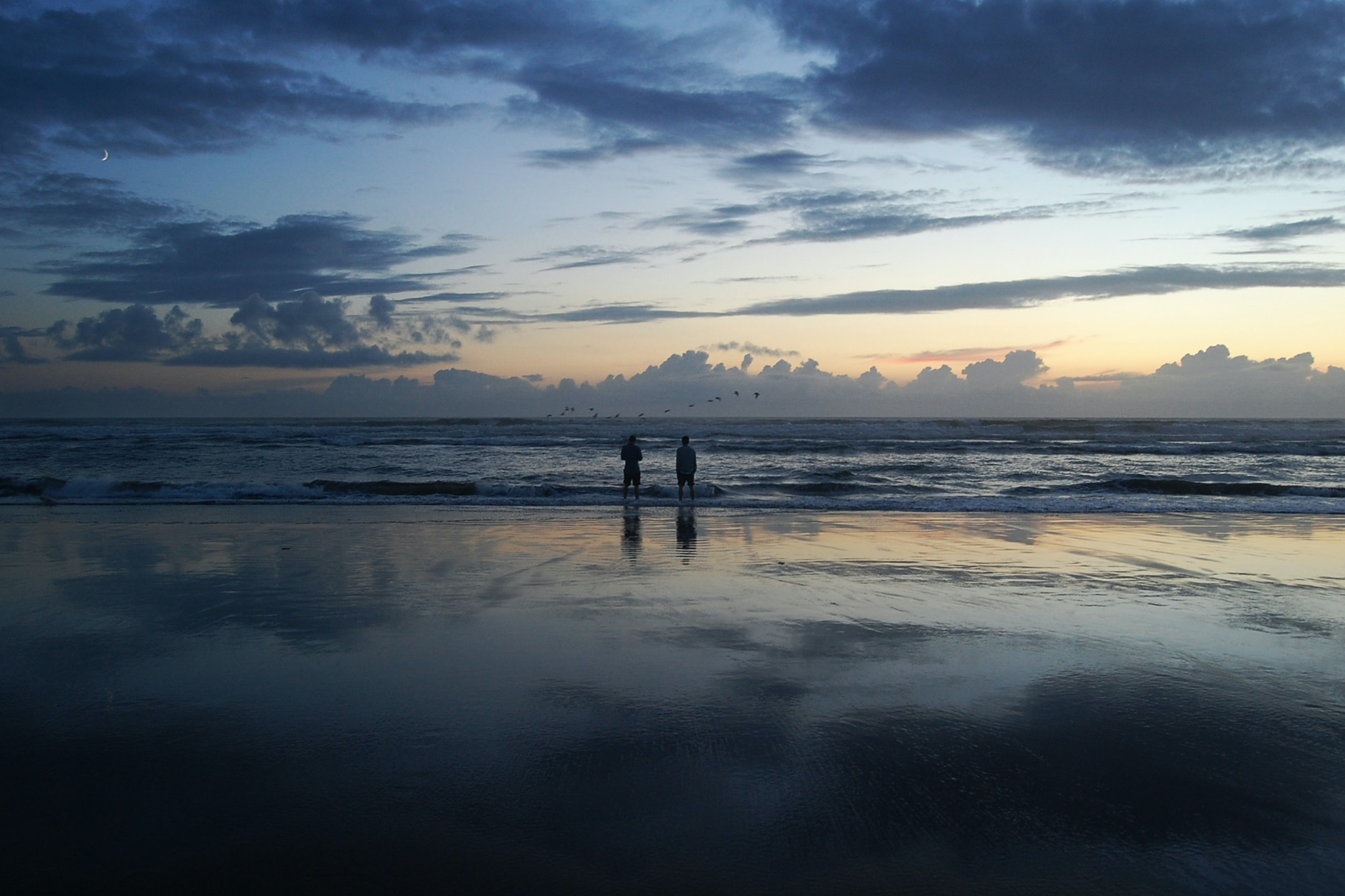 Two people standing on the beach looking out into the ocean at the horizon during sunset