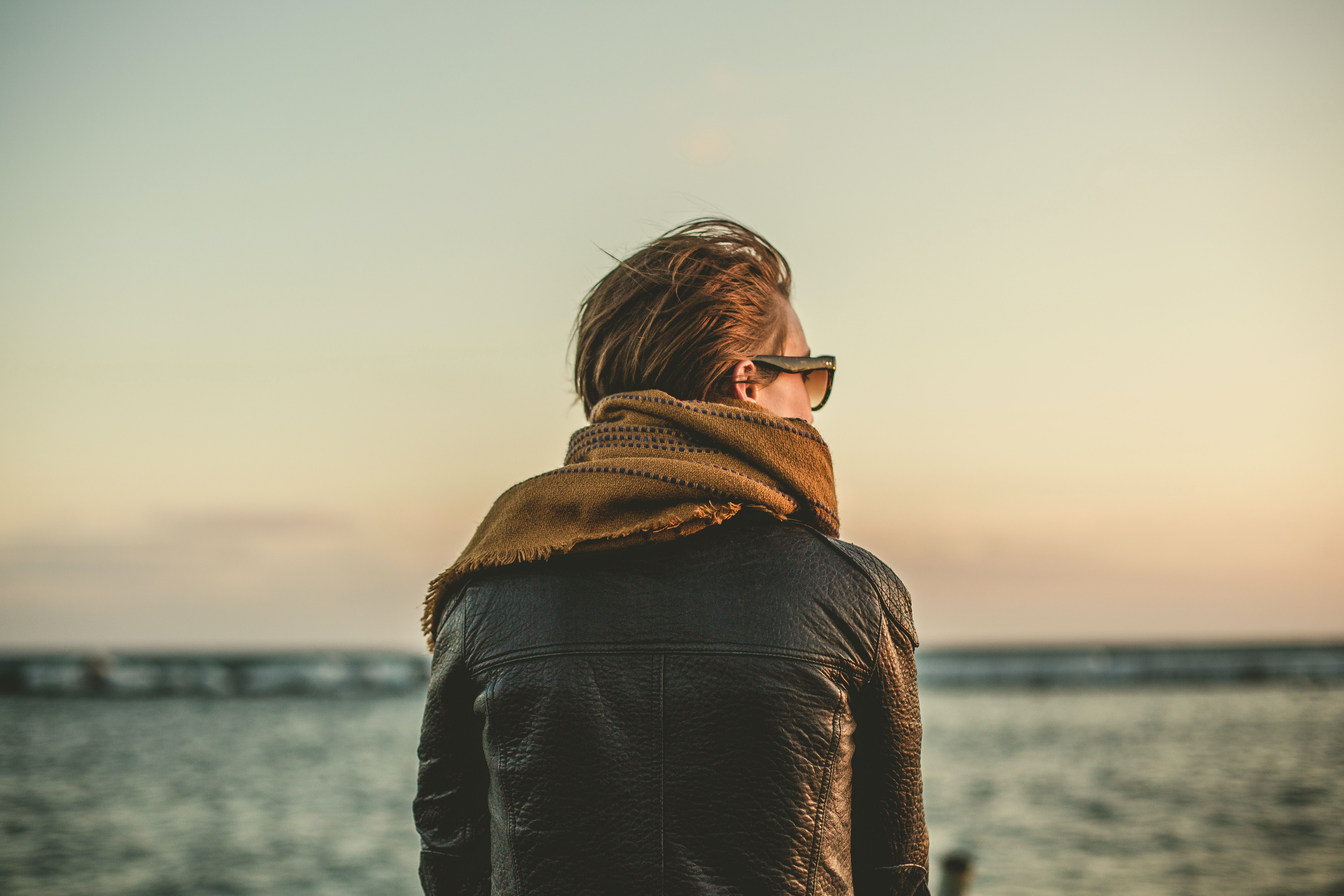 focus photo of person wearing black leather jacket with brown scarf near sea during daytime