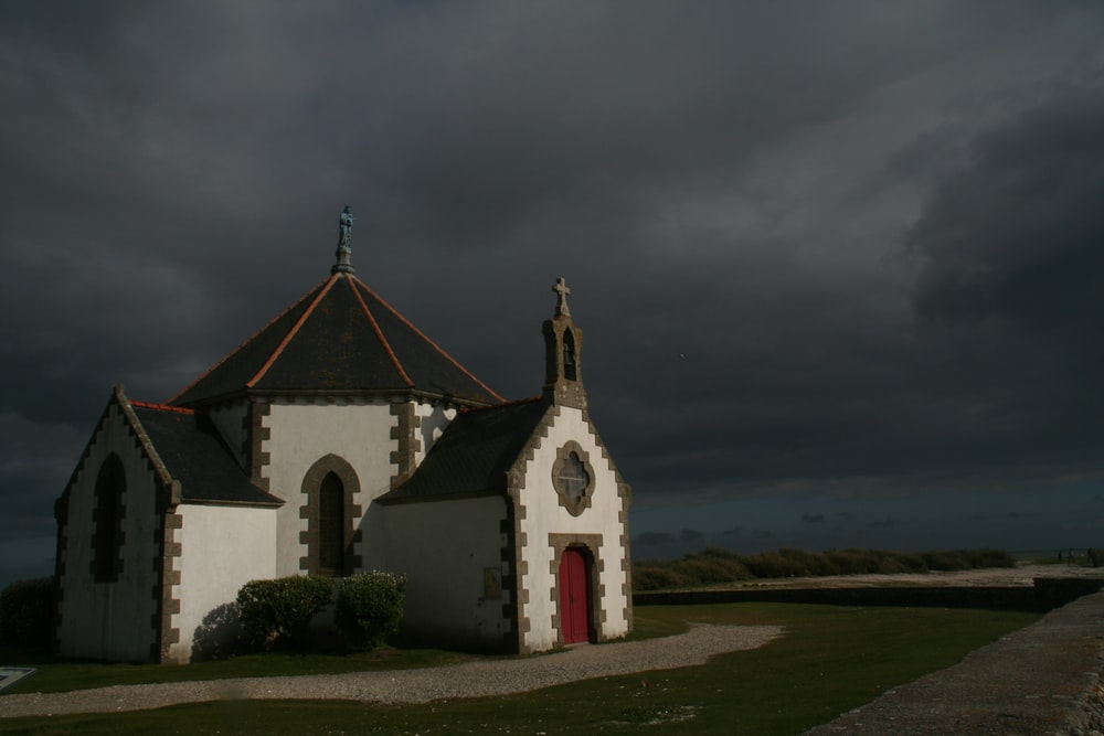 white and grey chapel surrounded by green grass field under grey cloudy sky