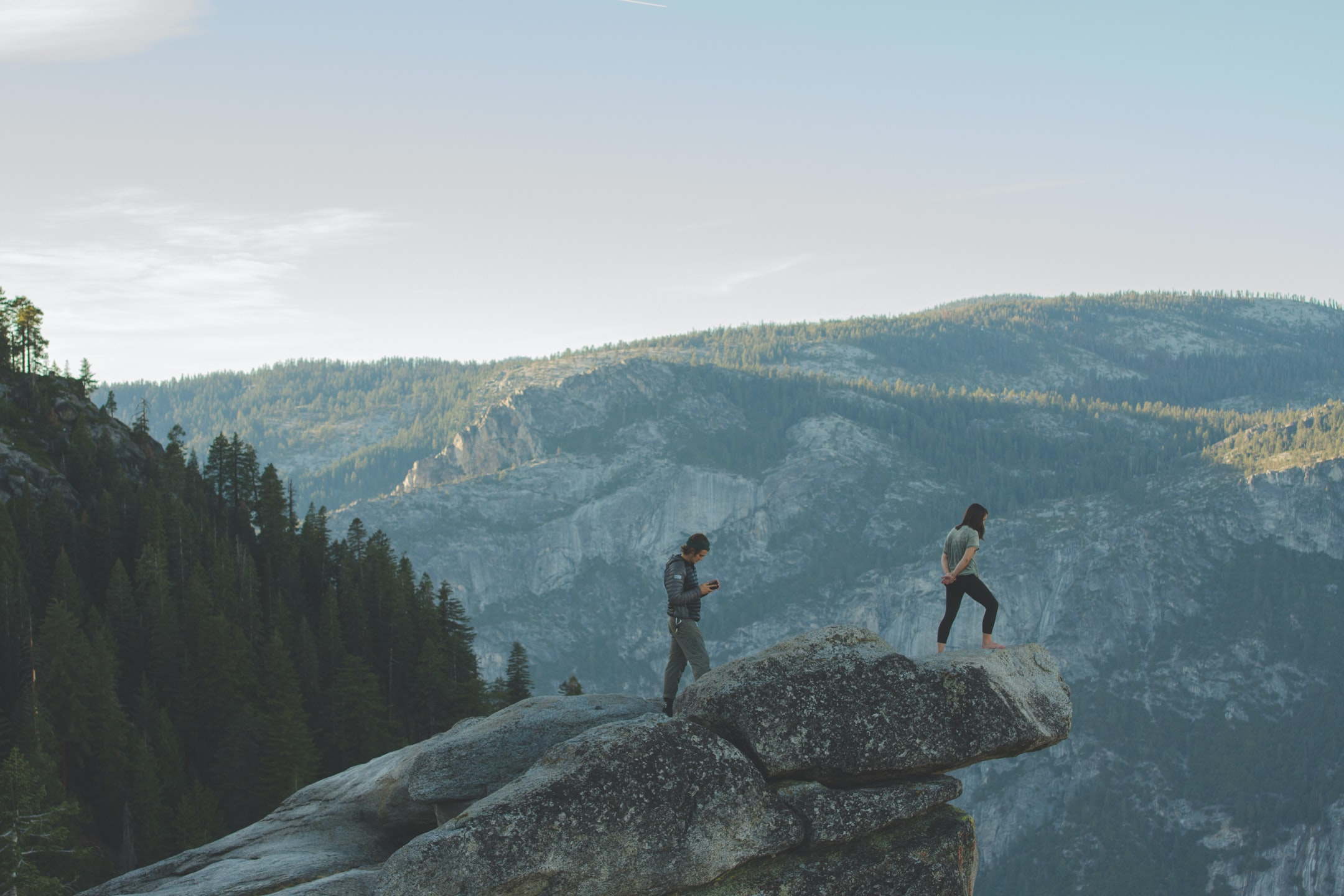 Extreme hikers peer over a rock ledge atop a mountain landscape