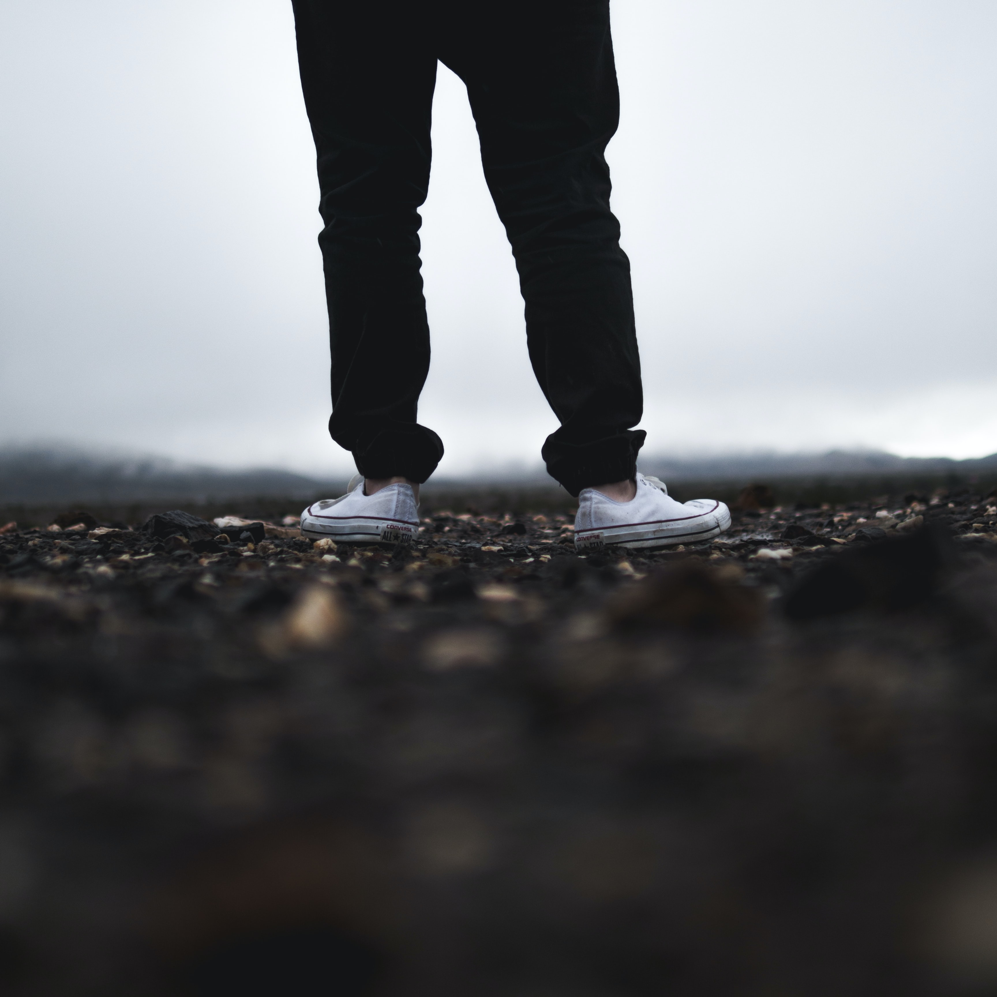 Low shot of person in converse sneakers standing on rocky ground