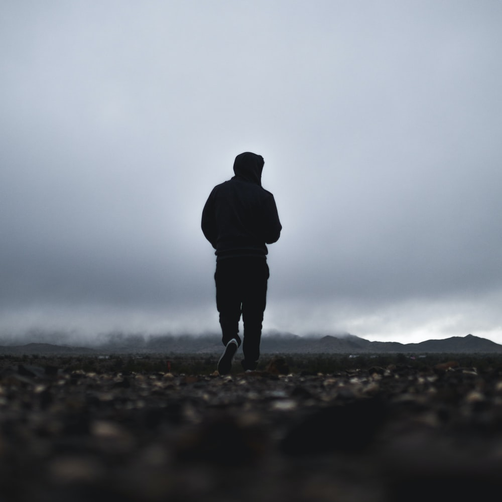 silhouette of person walking in front of mountain