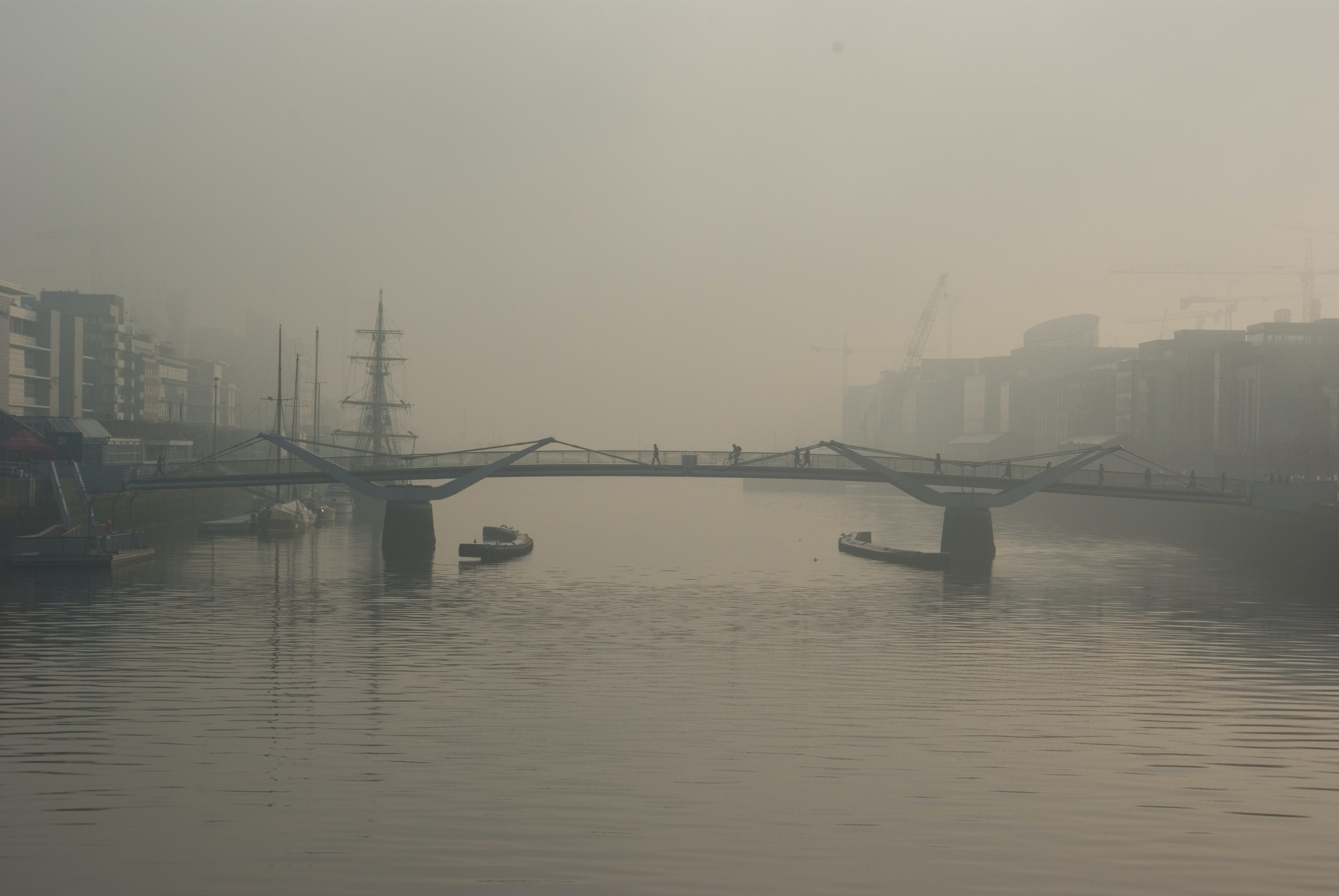 Industrial city structures by a bridge over foggy water