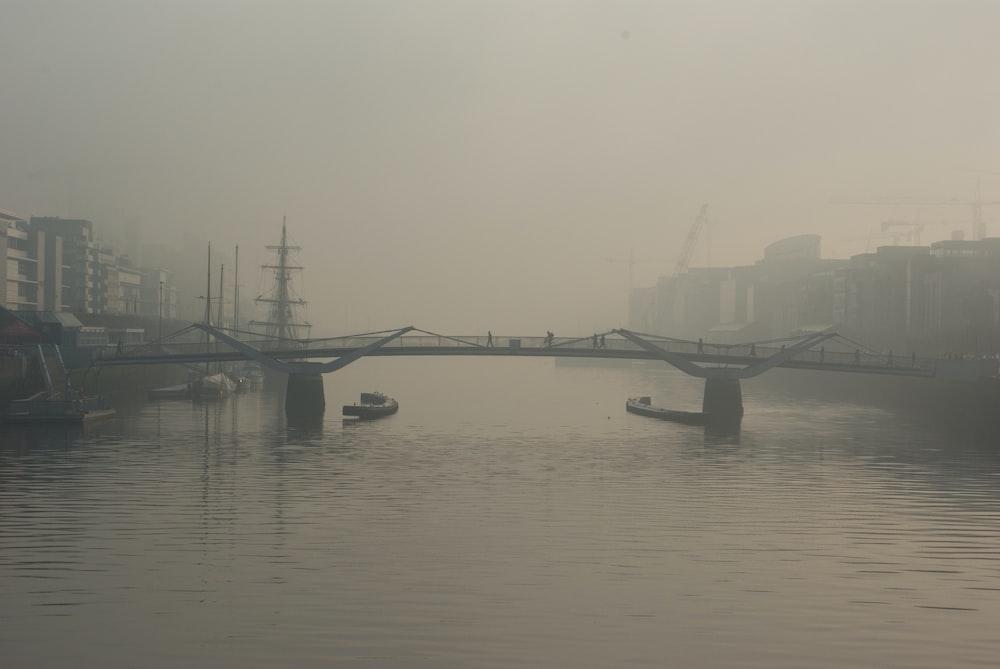 two boats below bridge with fogs