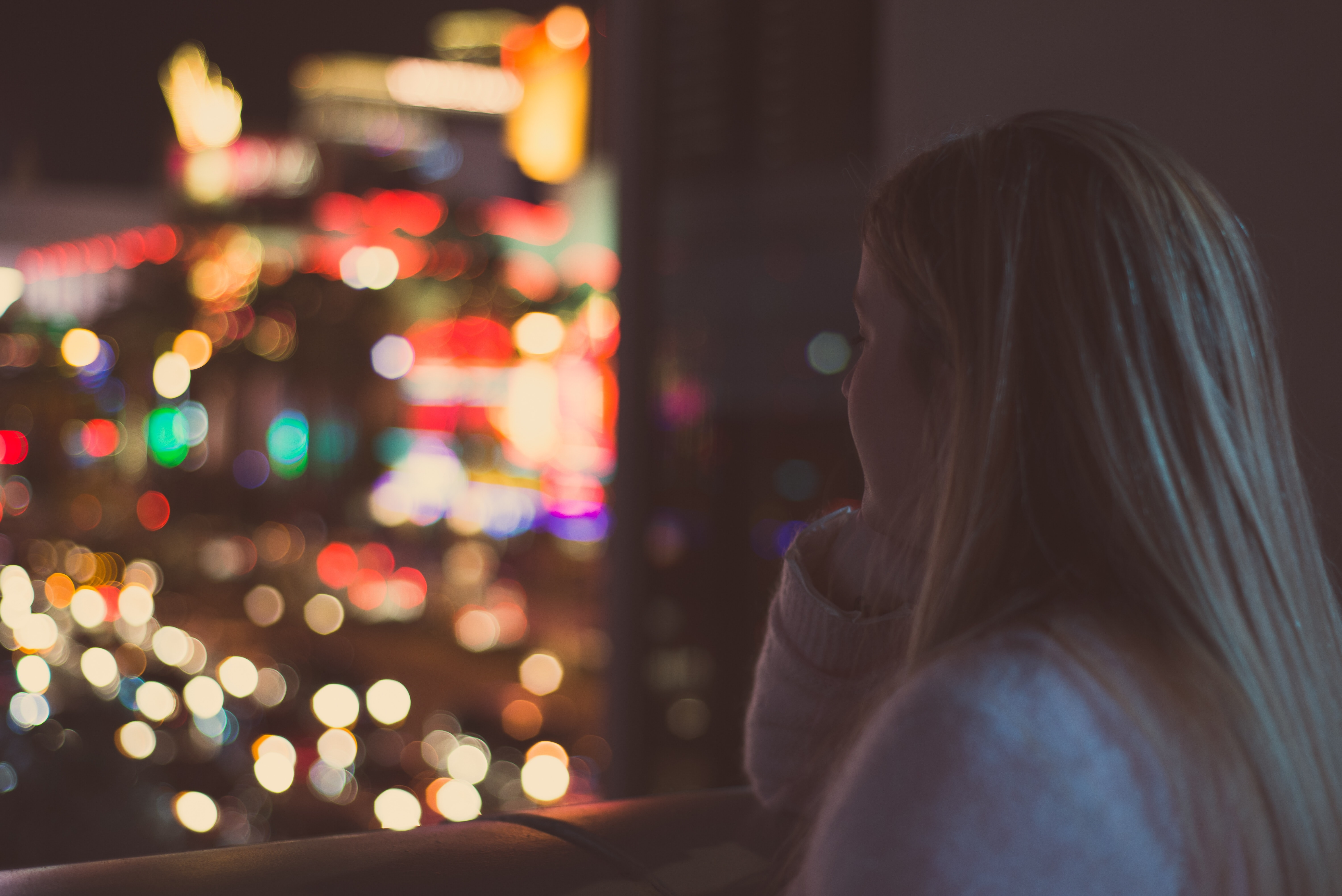 A girl with blonde hair peers out the window at a bokeh of city lights and traffic.