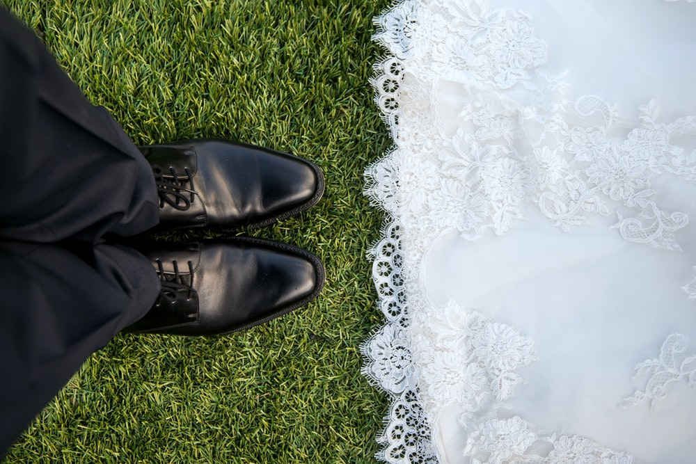 Bride wearing lace dress faces groom wearing black pants and shoes