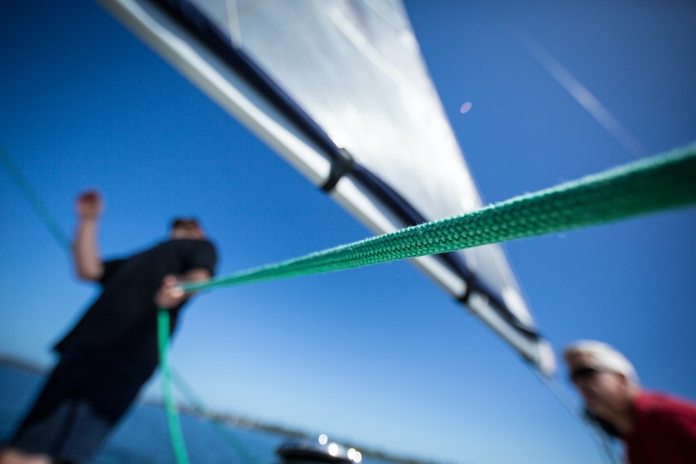 person holding green rope near boat sail