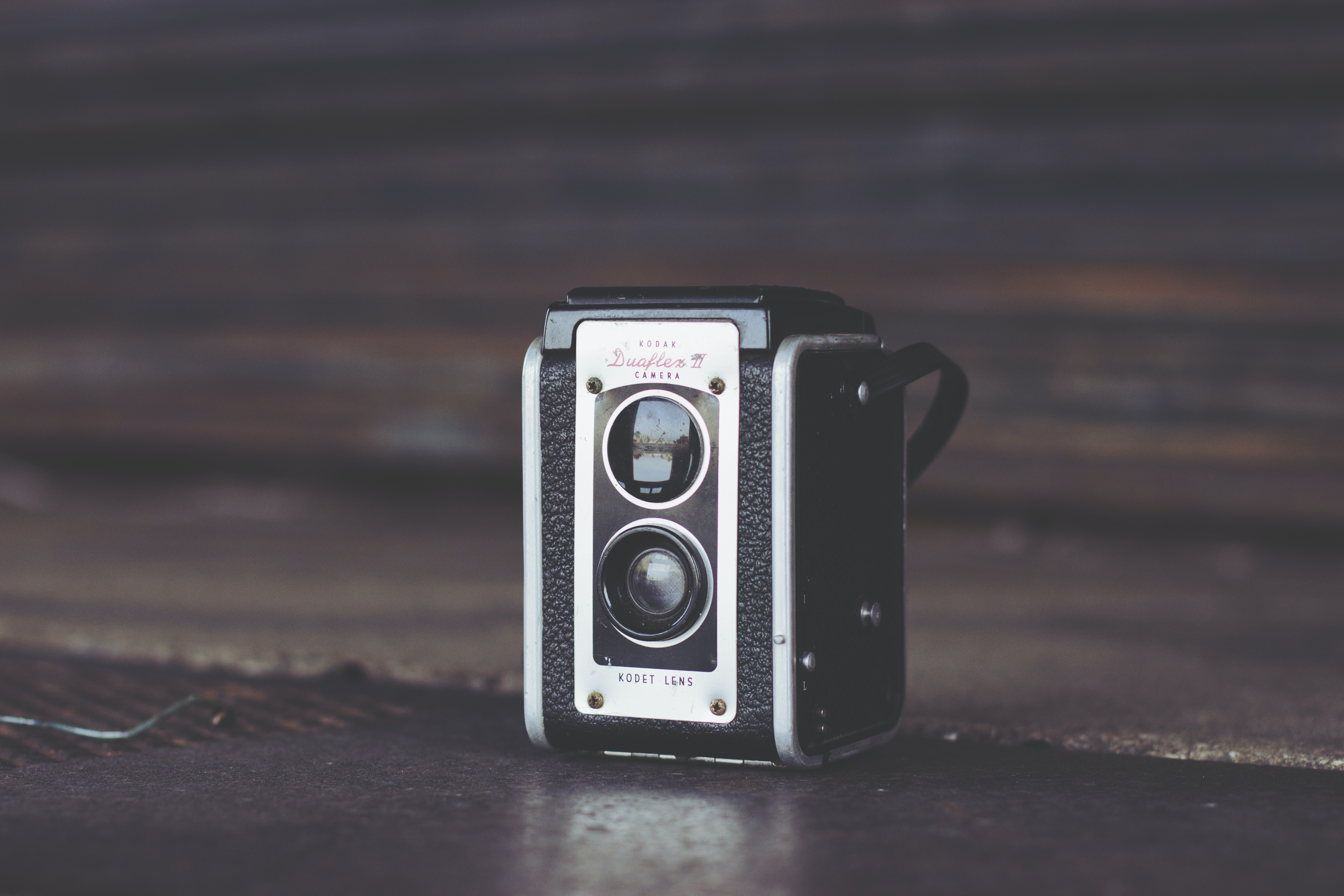 focus photo of black and gray vintage camera on brown surface