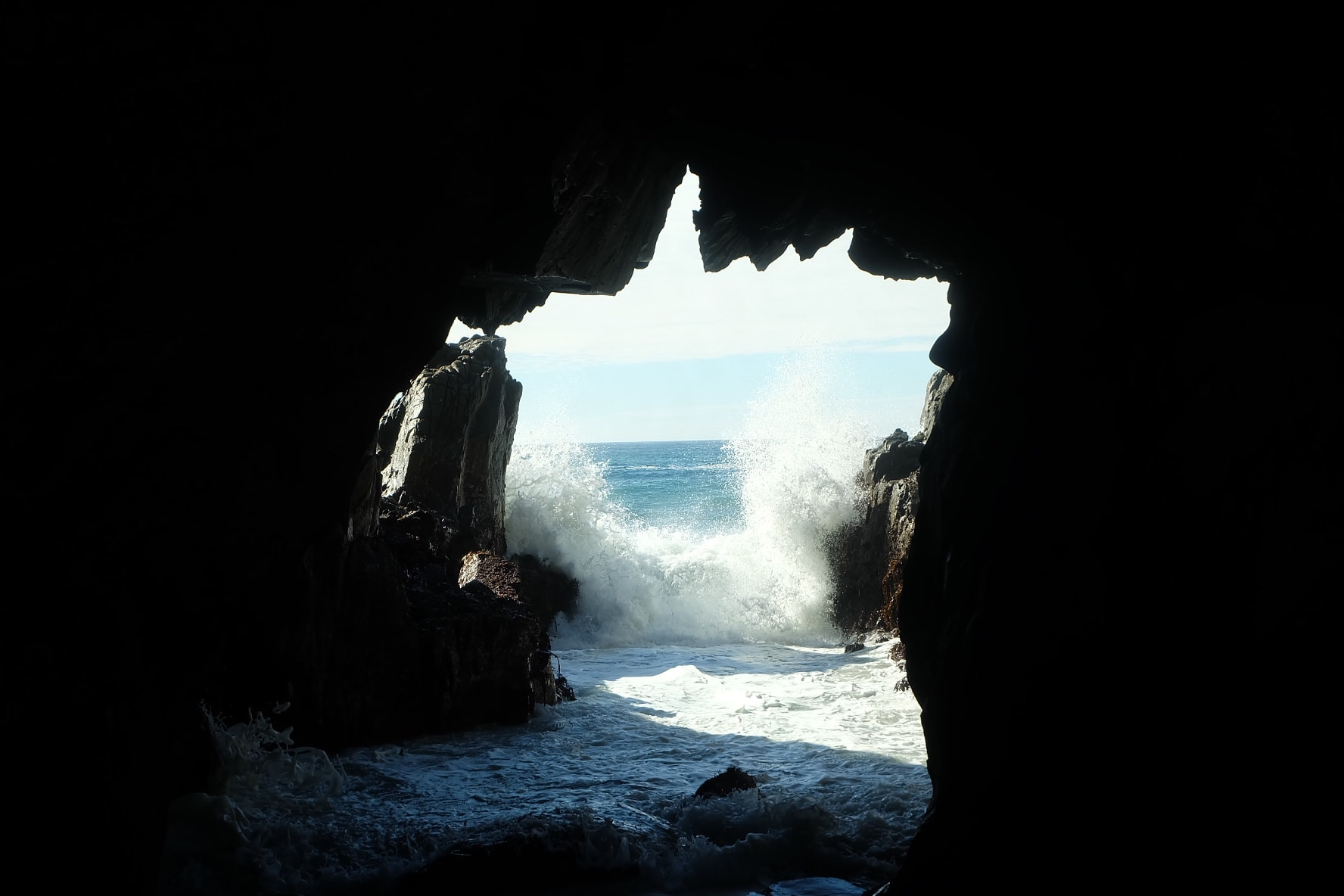 Sea waves splashing at the entrance to a dark sea cave
