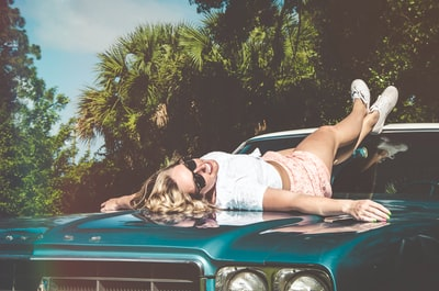 smiling woman lying on car with sunglasses