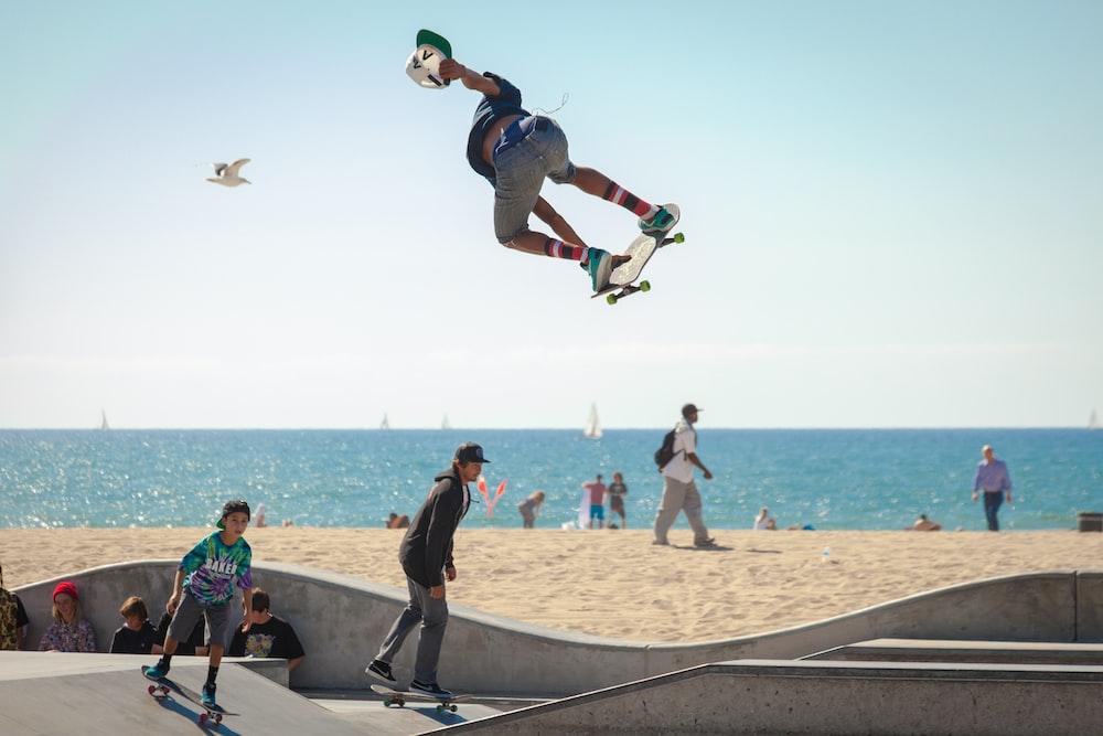 three people playing skateboard beside seashore during daytime