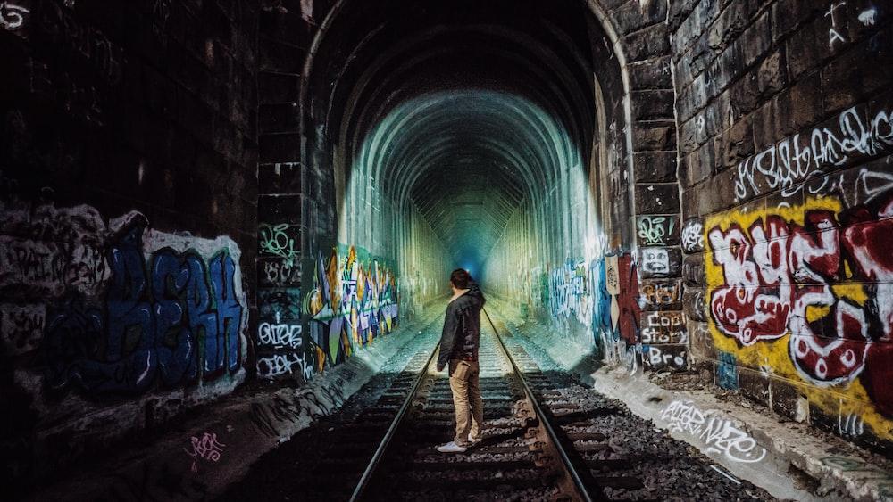 man standing near tunnel